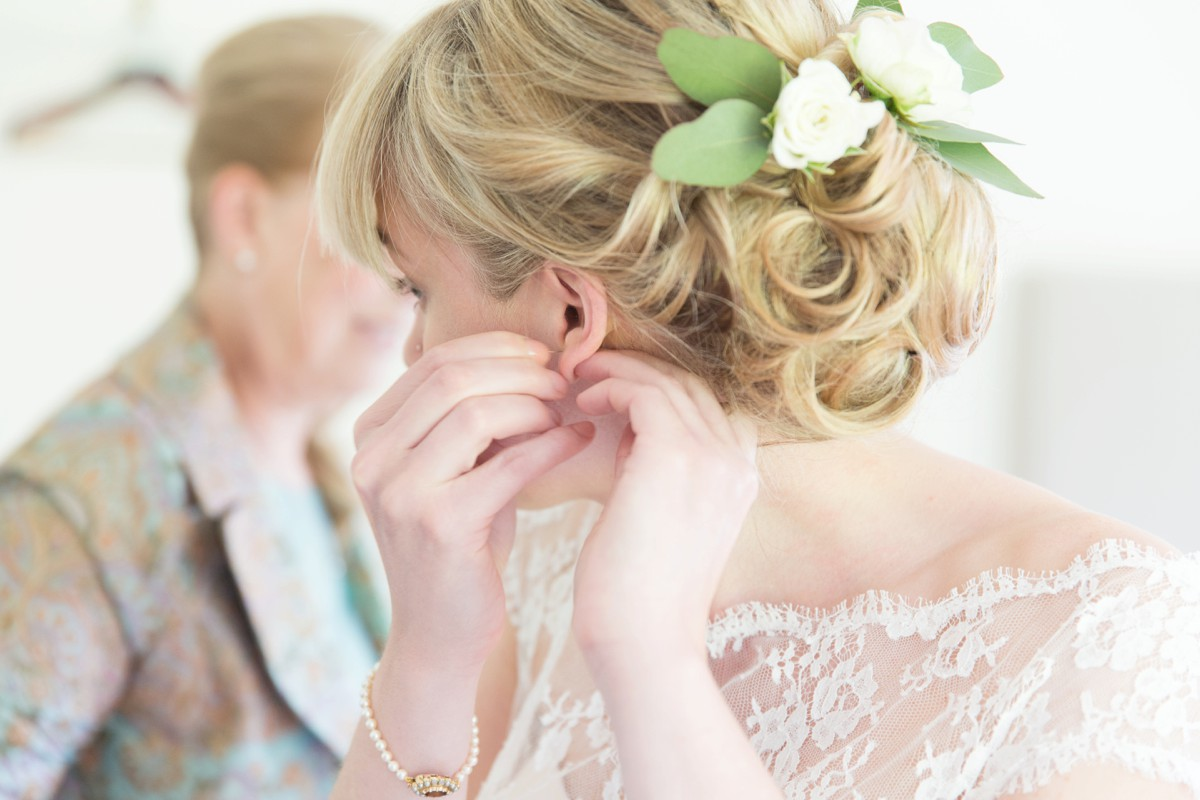 bride putting wedding earrings on