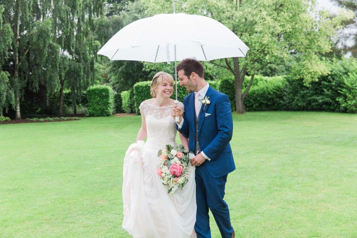 bride and groom walk with umbrella at Nymans Gardens