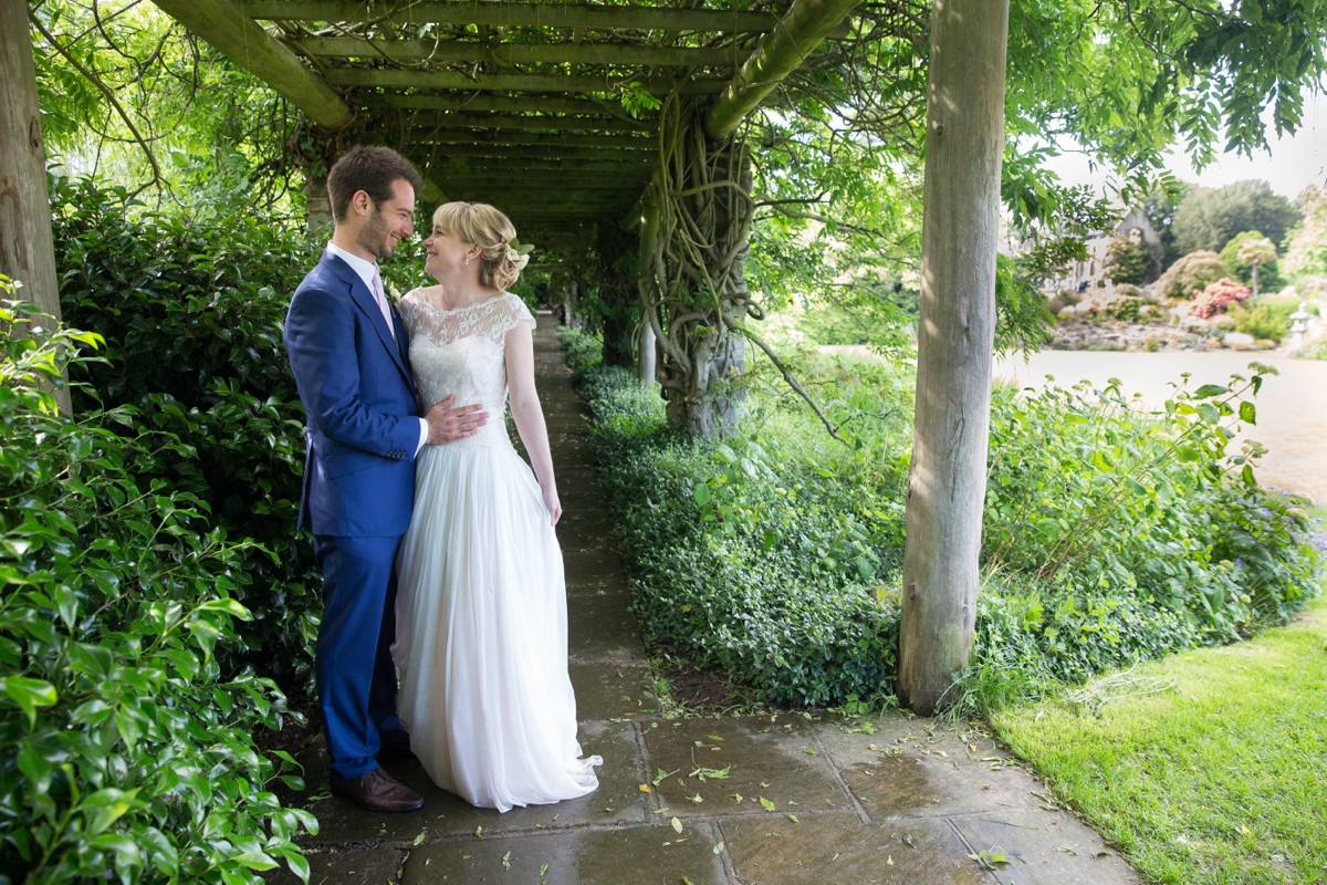 bride and groom stand under arbour at Nymans House