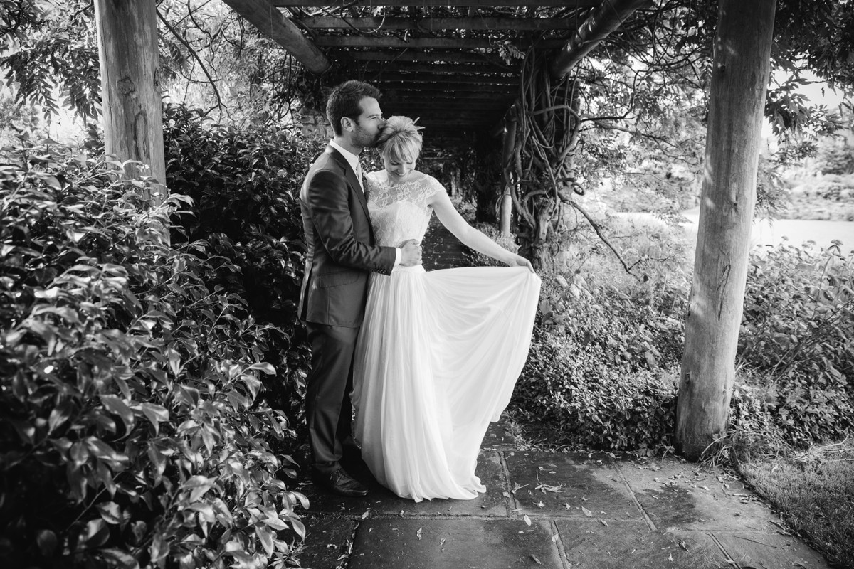 black and white shot of bride and groom standing in Nymans Garden