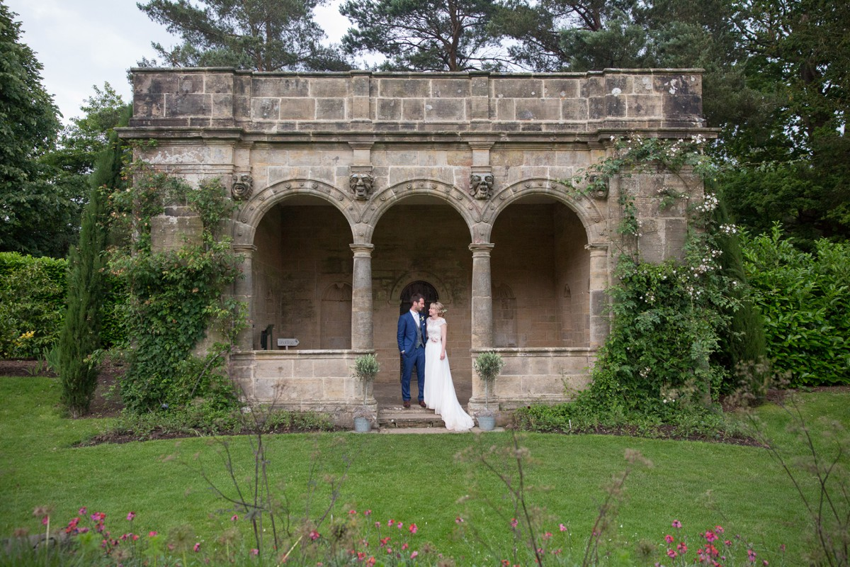 bride and groom stand together outside open national trust building at Nymans gardens in East Sussex