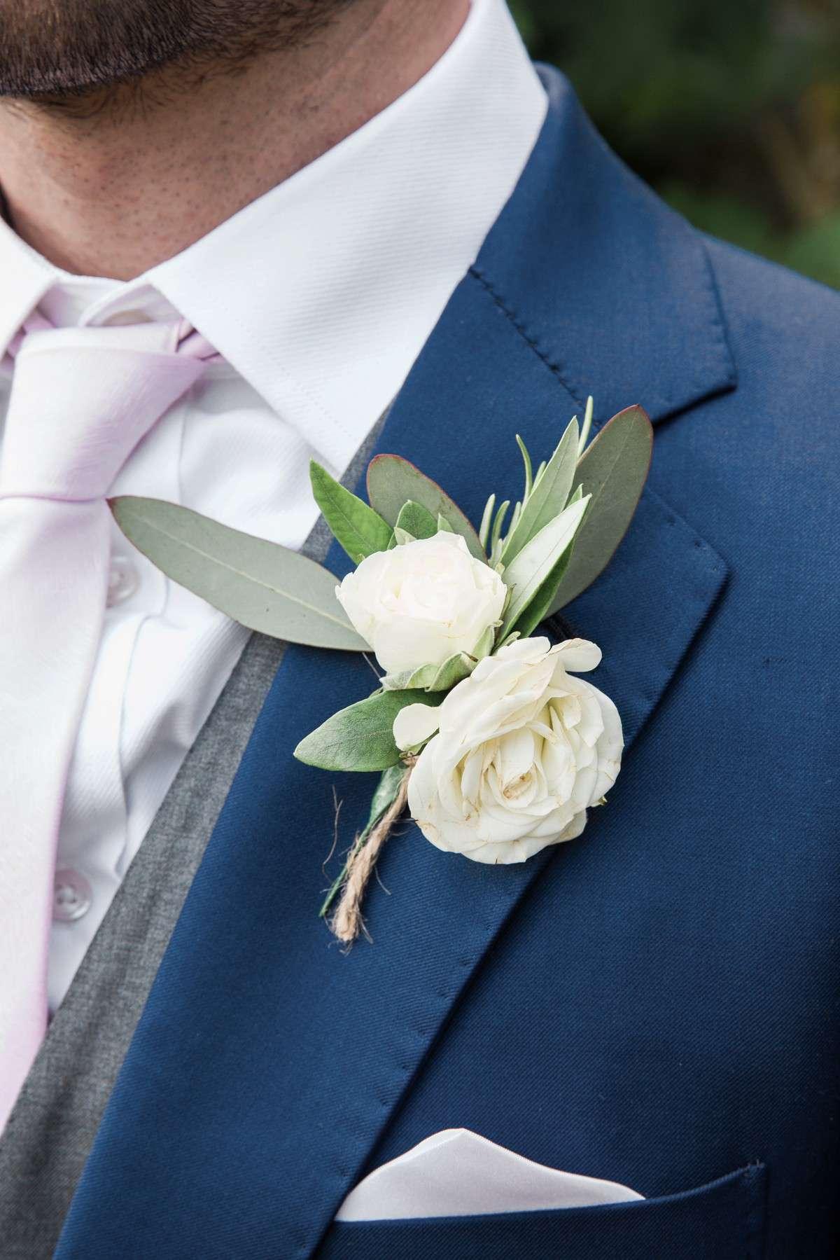 white buttonhole with dark blue jacket wedding suit