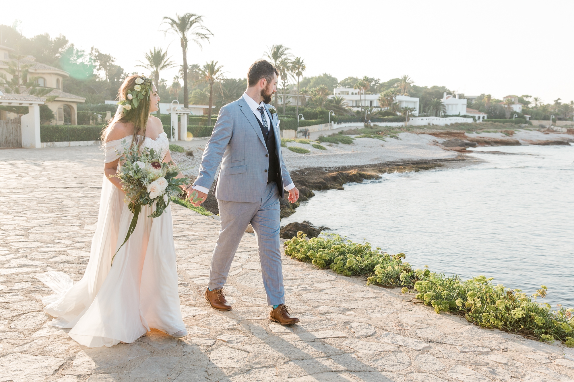 bride and groom walk along ocean at Denia, Spain