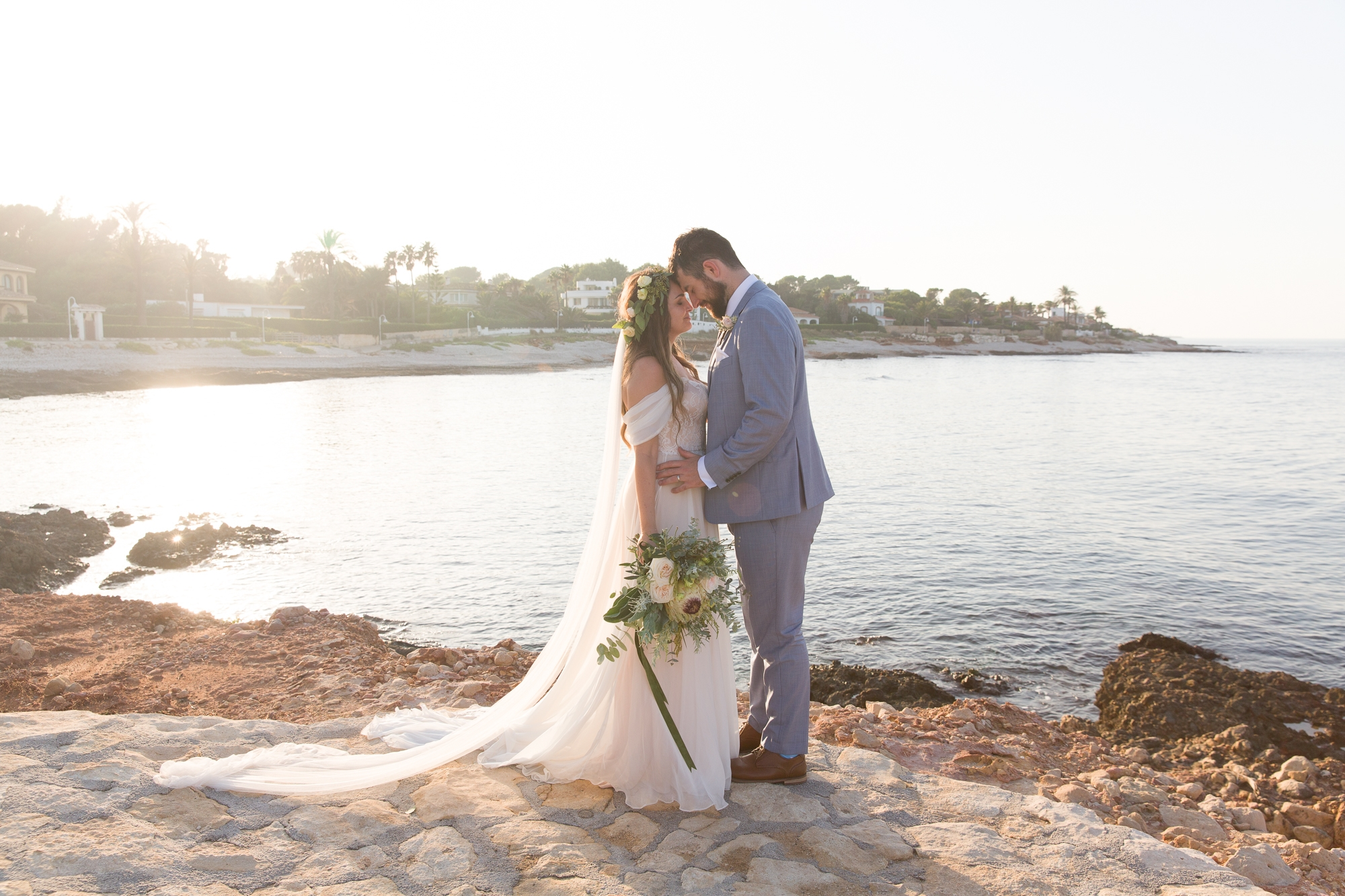 couple put heads together by ocean at destination wedding in denia spain