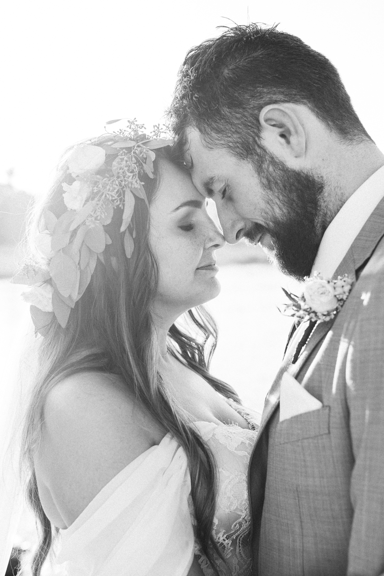 bridal couple touch heads together by the ocean at their destination wedding spain