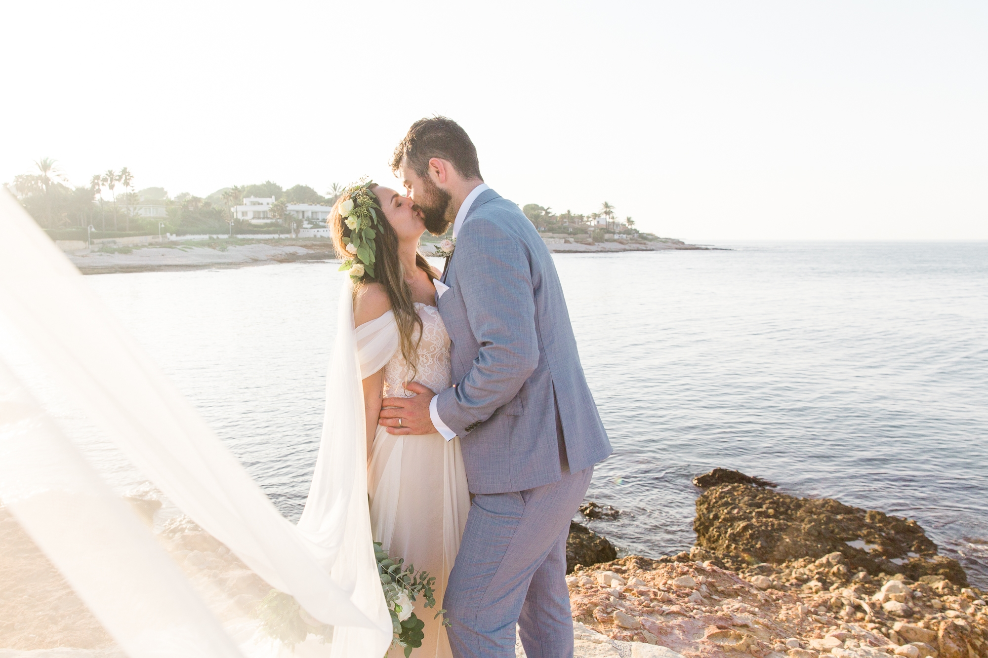 sunlight catches the brides veil as she kisses her husband by the sea in Spain