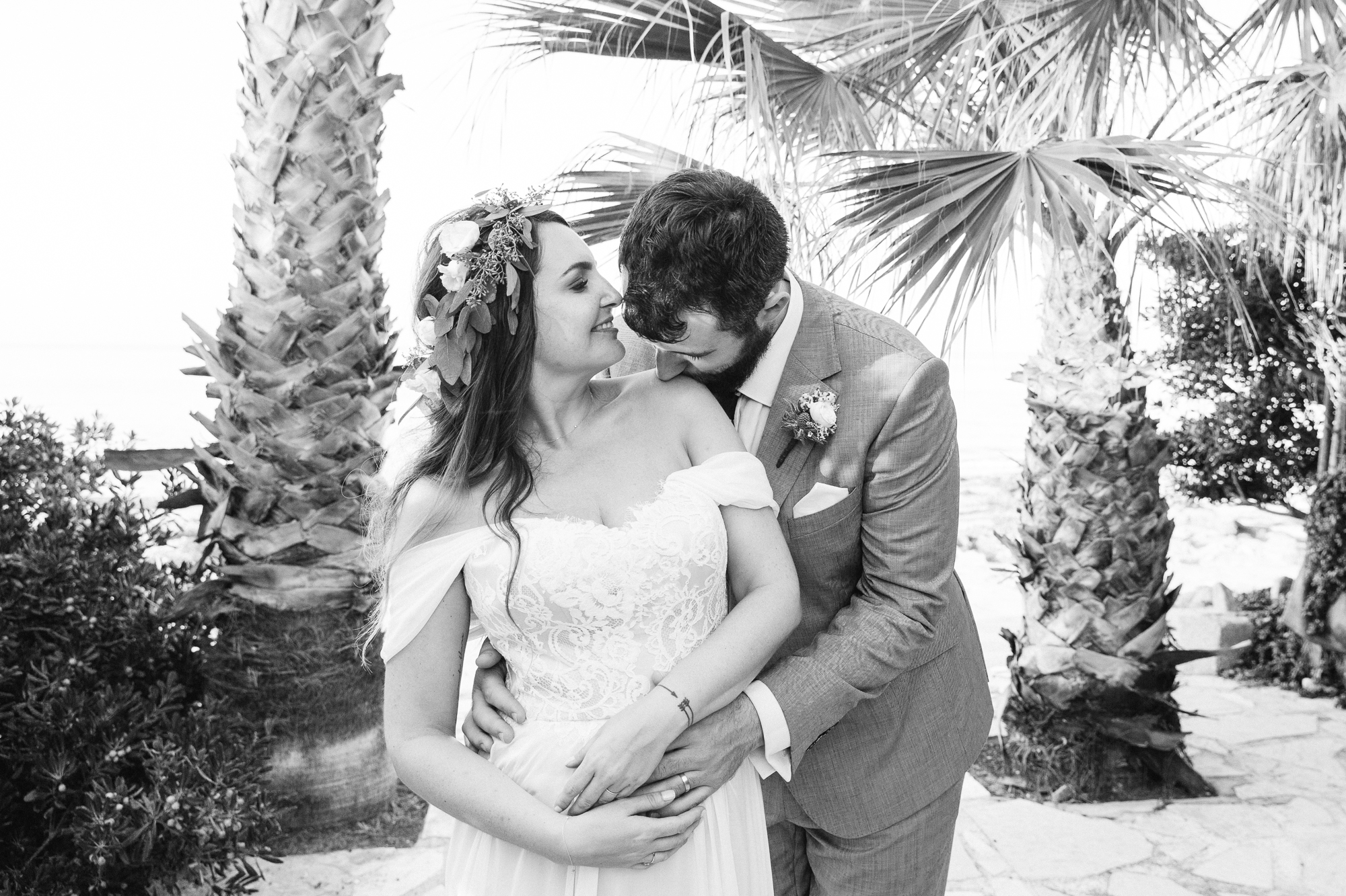 groom kisses brides shoulder in front of palm tress in denia, spain