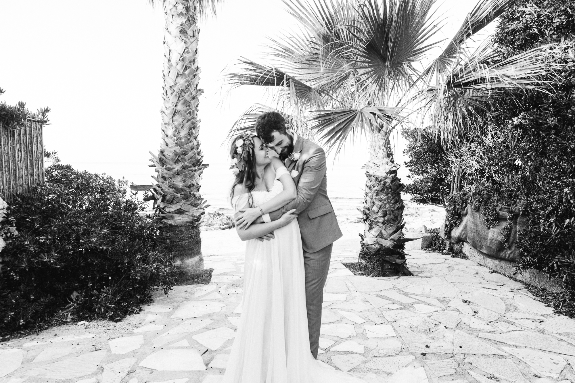 wedding couple embrace in front of palm tress in denia, spain