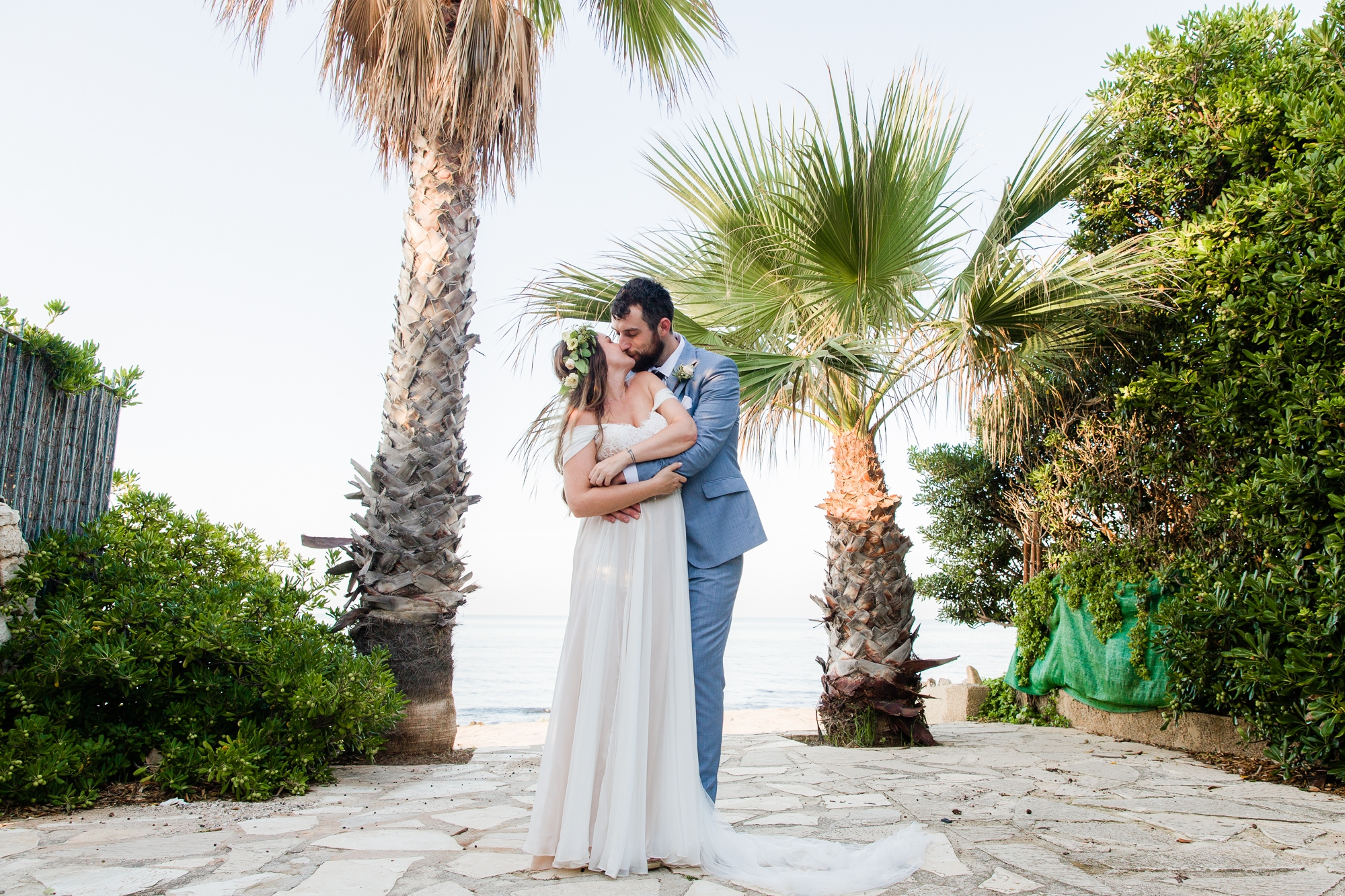 wedding couple kiss in front of palm tress in denia, spain