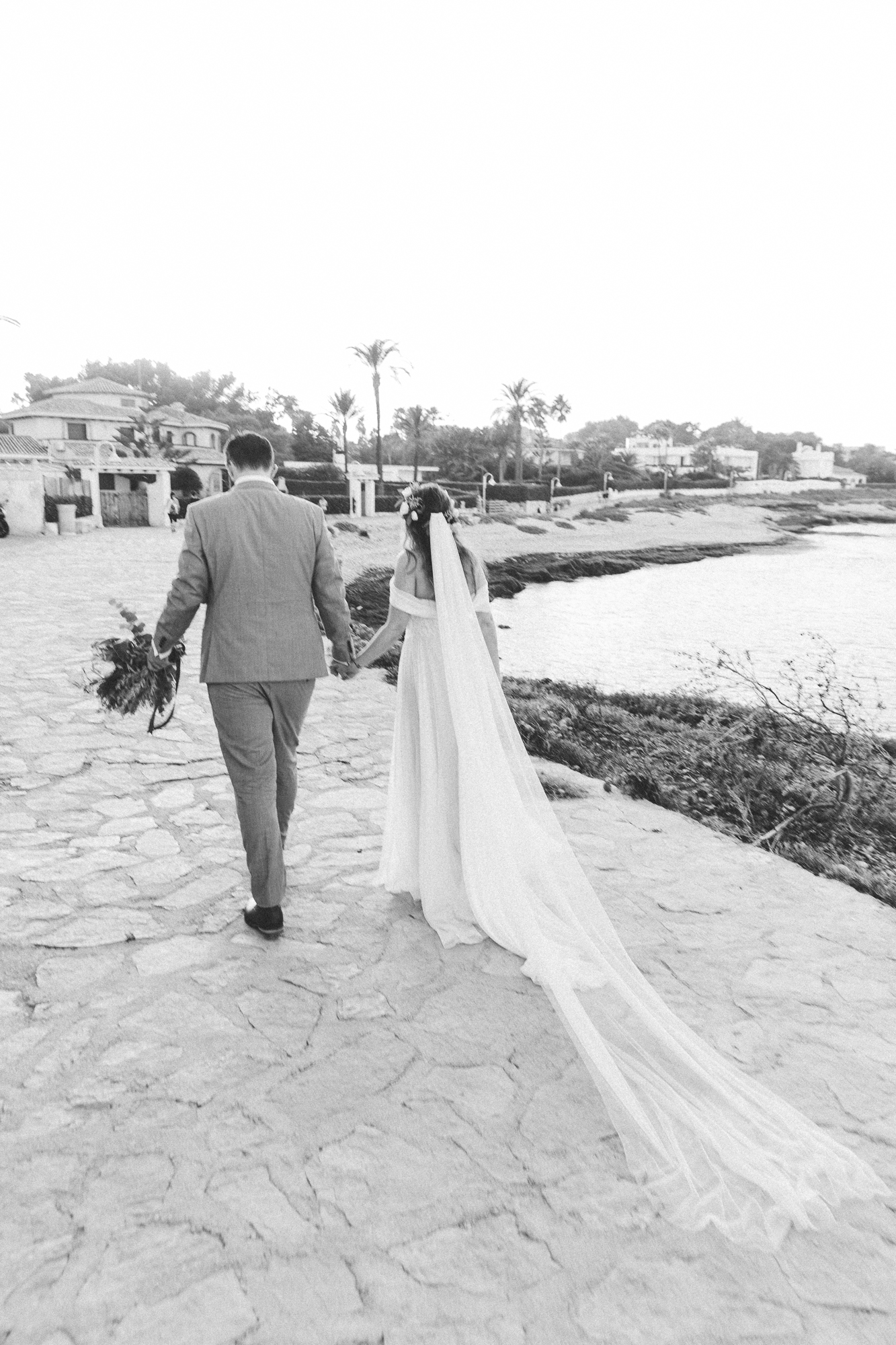 couple at Spanish destination wedding walk away towards the sea at Denia wedding