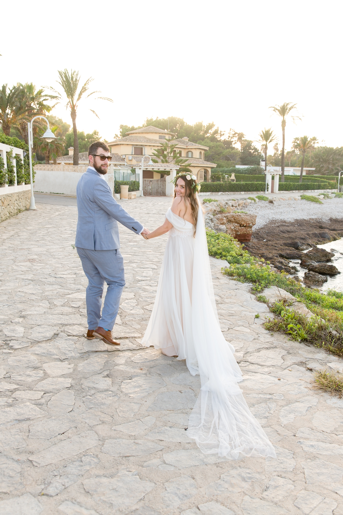 bride and groom look back as they walk by the sea at Denia wedding