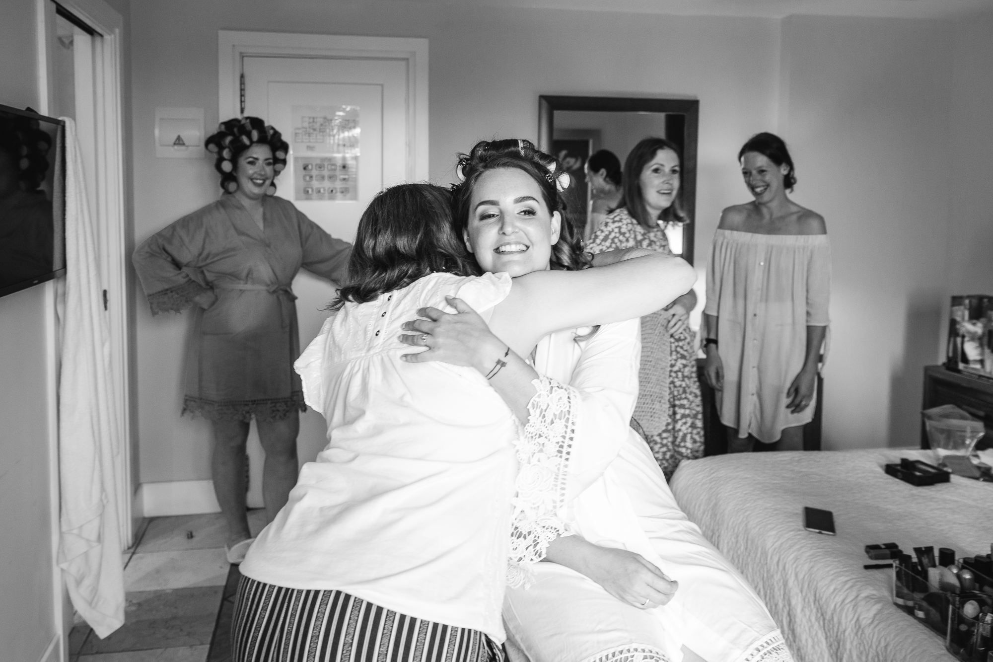 Mother hugs bride as she sits in Hotel Les Rotes, Denia wedding