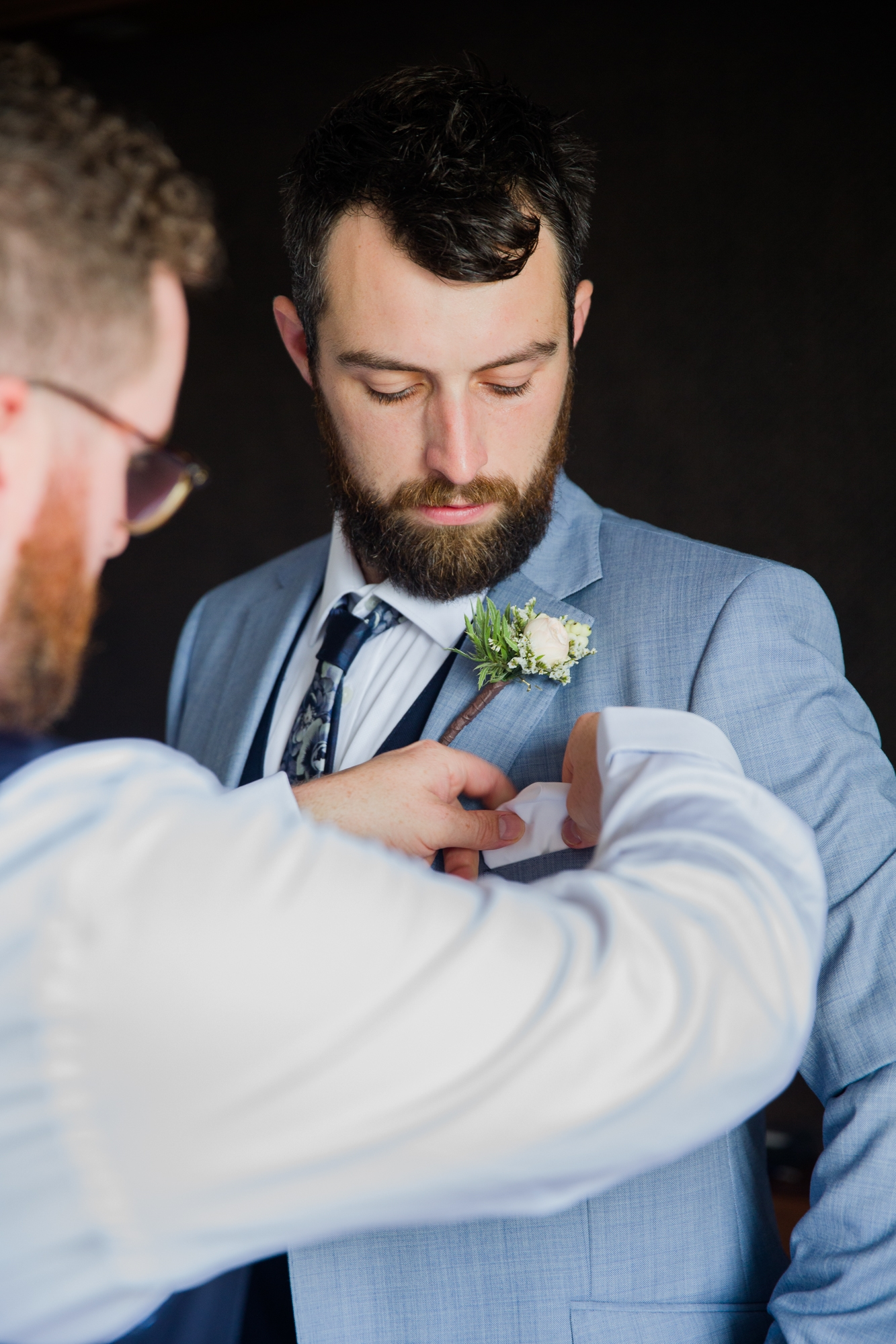 Groom in light blue suit attaches buttonhole at Hotel Les Rotes, at destination wedding Denia