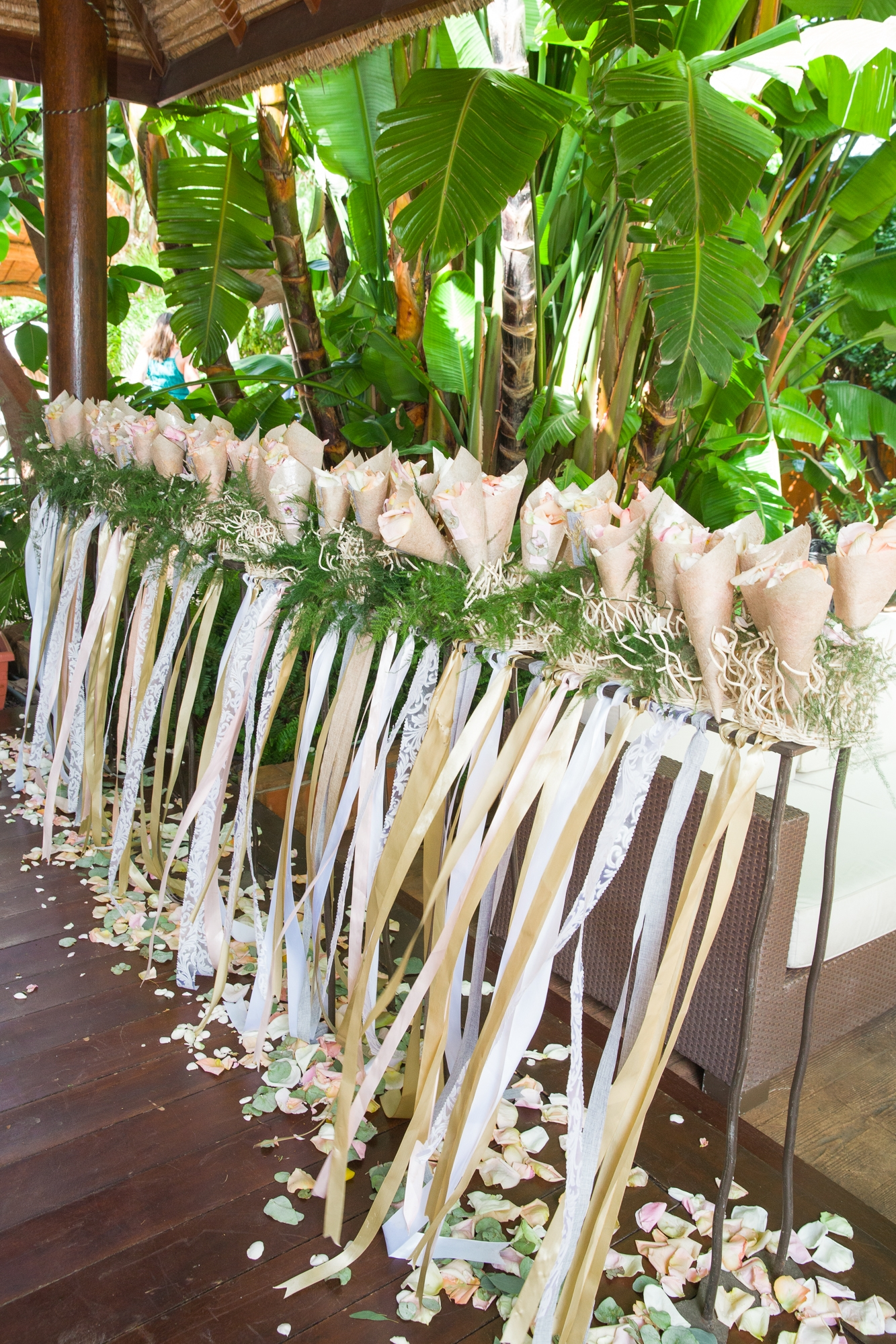confetti cones sitting on a long stand with wedding ribbons