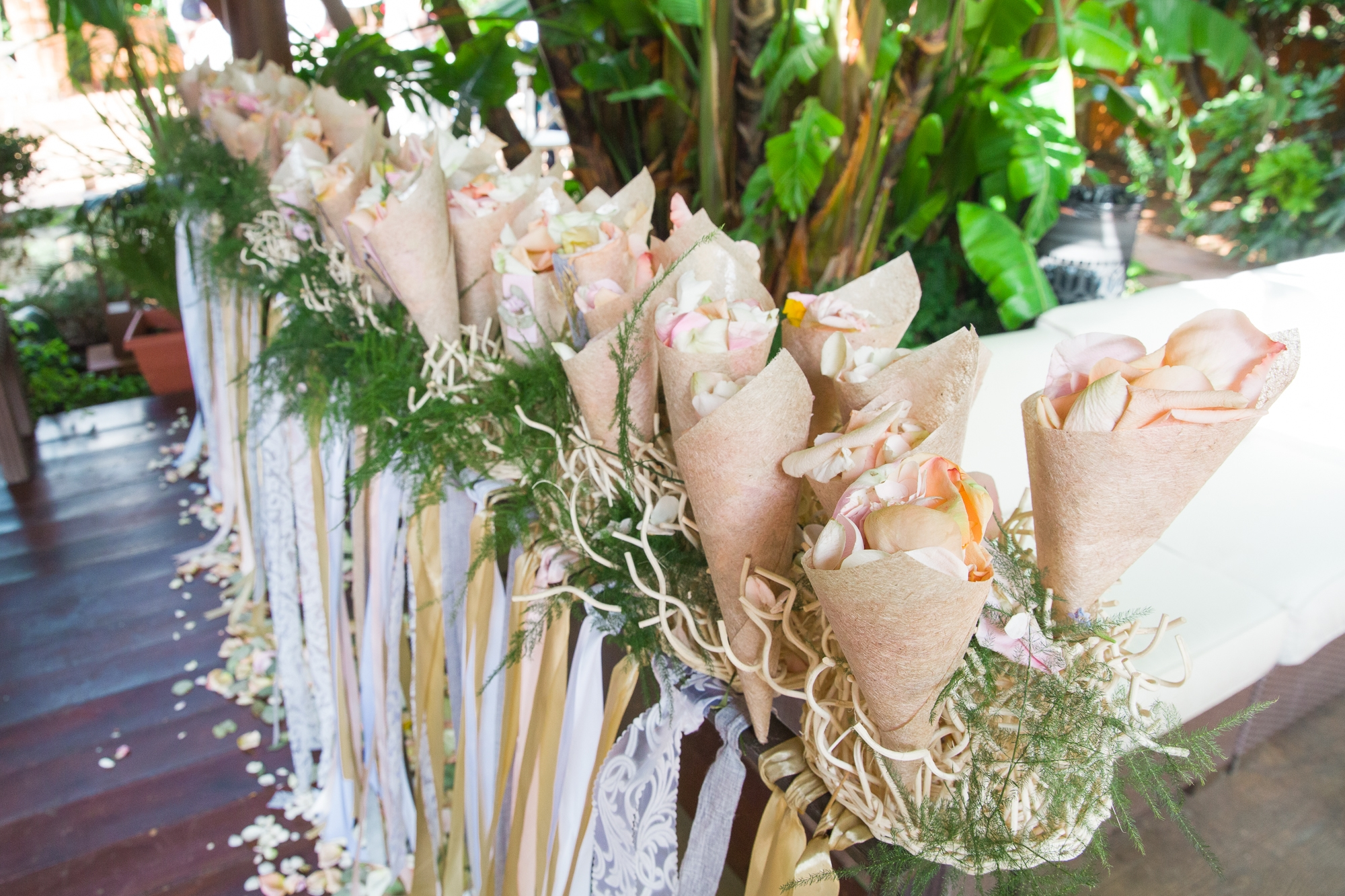 confetti cones sitting on a long stand with white and yellow wedding ribbons
