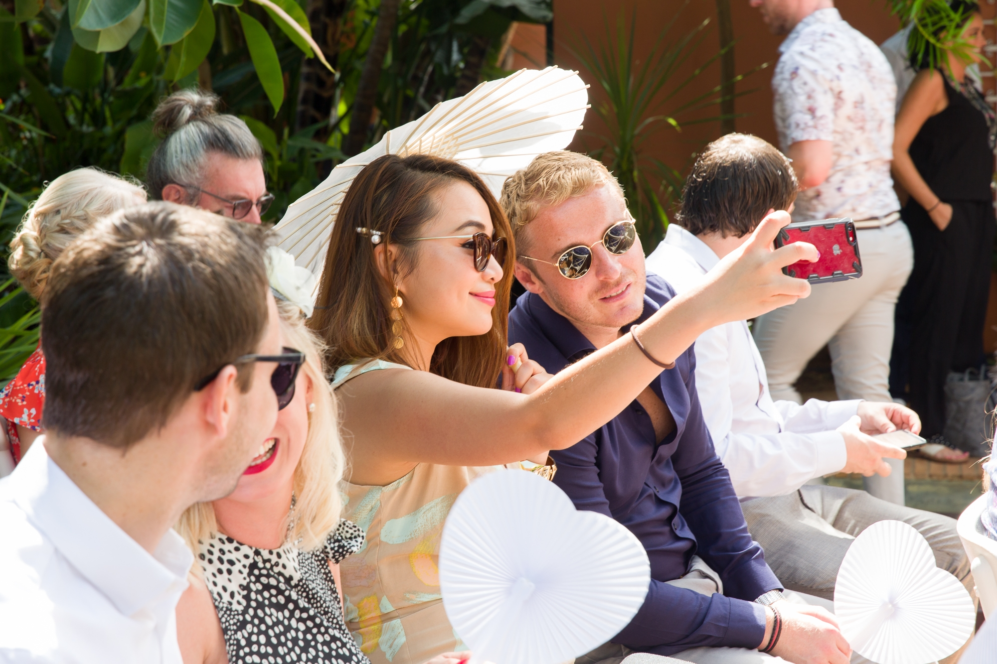 Guests with white parasol take a selfie at this Spainish destination wedding