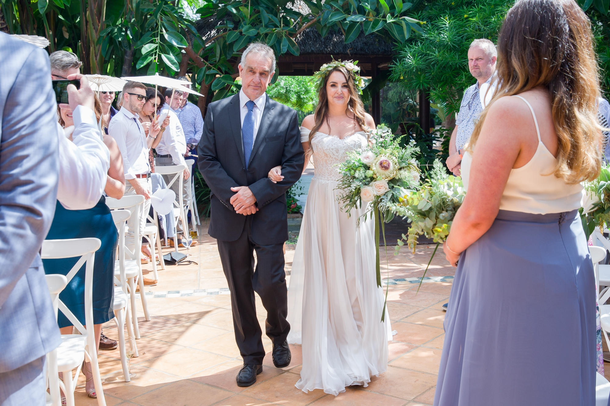 bride walks up the aisle at Hotel Les Rotes with her father at wedding in Spain
