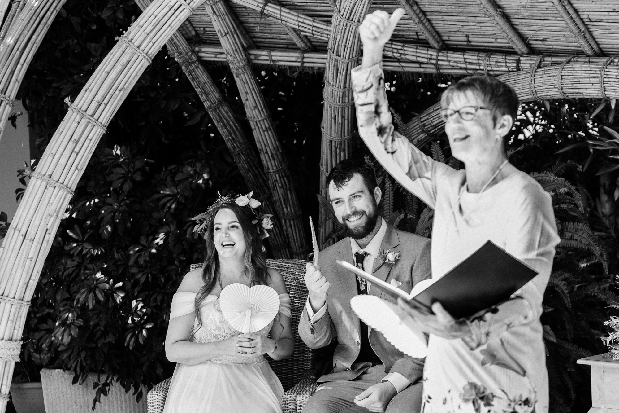 bride and groom sit as celebrant thumbs up at Hotel Les Rotes, Denia