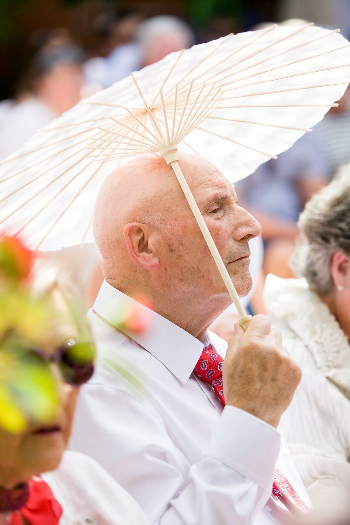 man sits at wedding in Denia holding a white parasol
