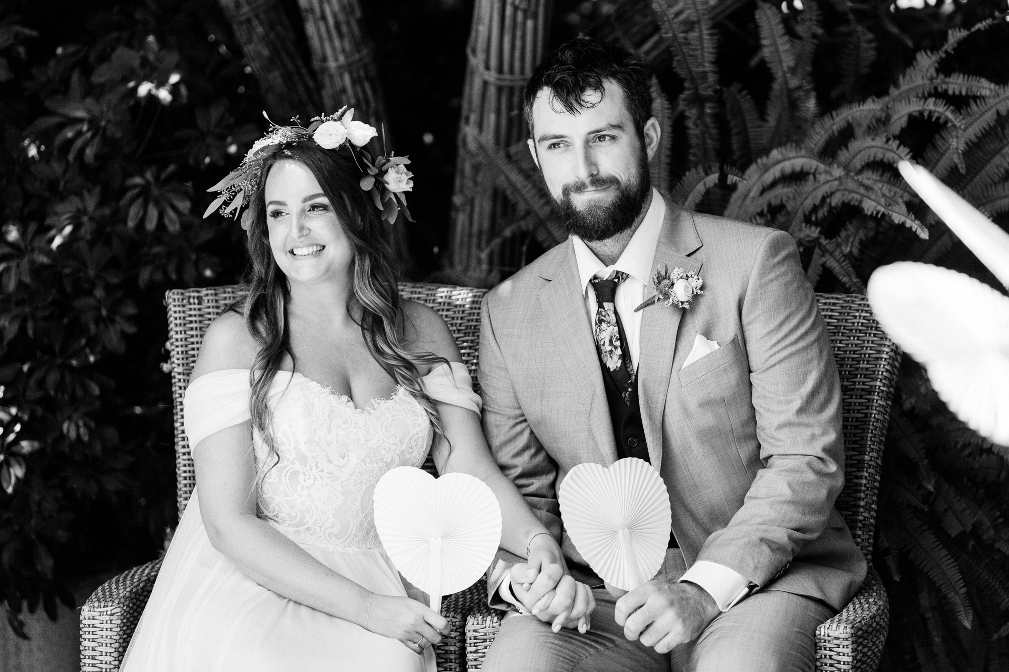 bride and groom sit outside at Hotel Les Rotes in Denia holding white heart-shaped fans