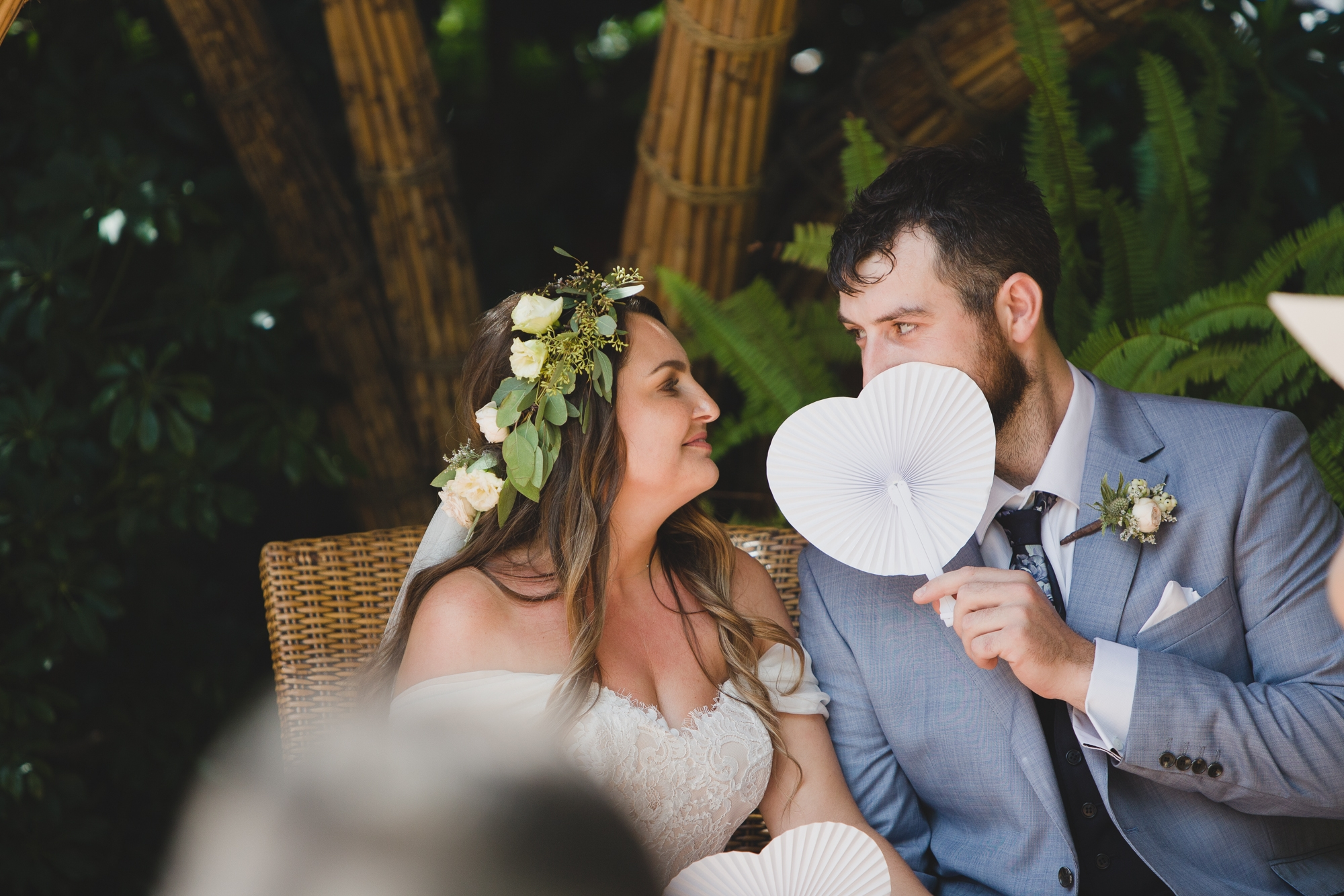 wedding couple sit at Hotel Les Rotes in Denia holding white heart-shaped fans