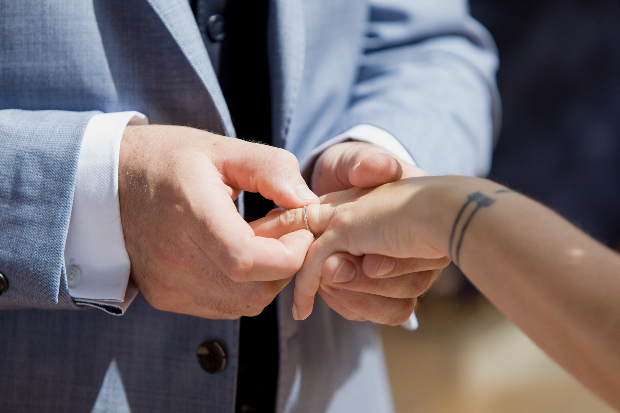 groom puts wedding ring on his brides finger at Hotel Les Rotes