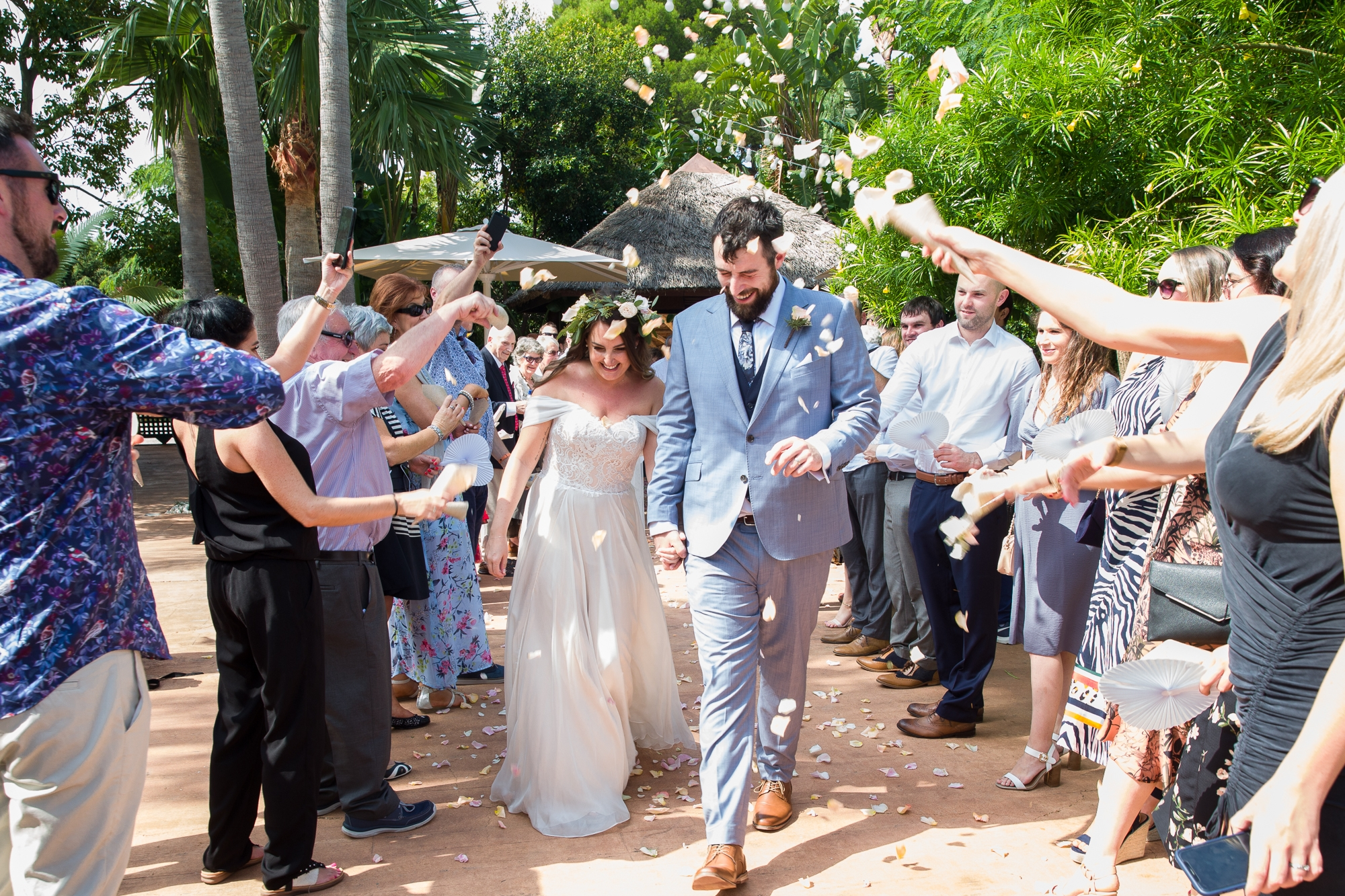 bridal couple walk through confetti tunnel at Hotel Les Rotes in Destination wedding in Spain