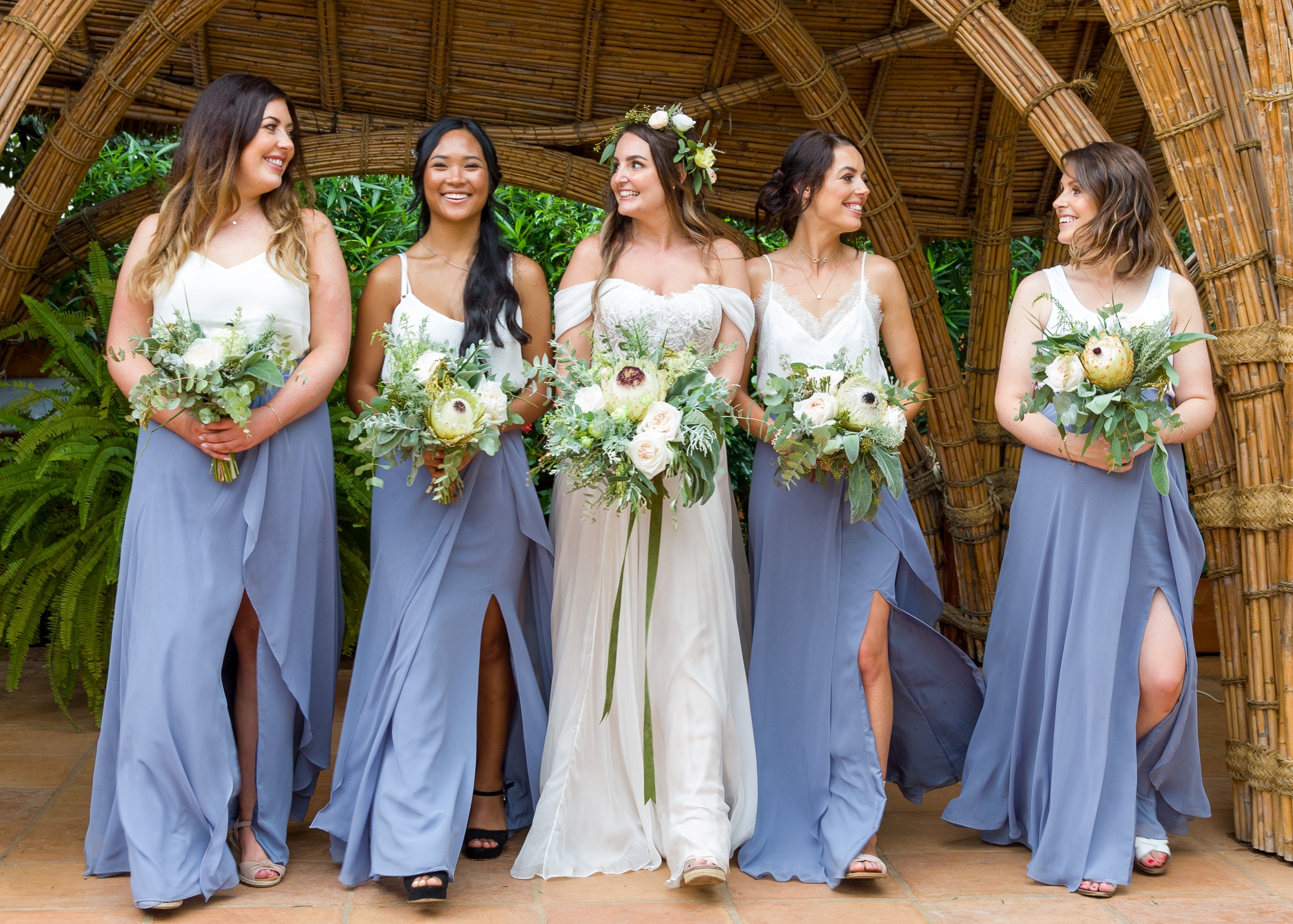 Bride in Moira Hughes wedding gown and bridesmaids with blue skits holding bouquets look at each other