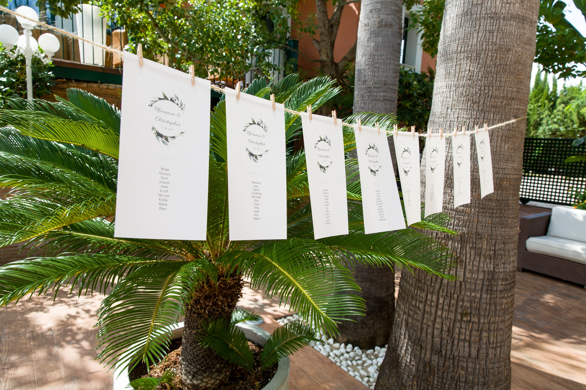 wedding table plan hangs across palm trees at Hotel Les Rotes, Denai