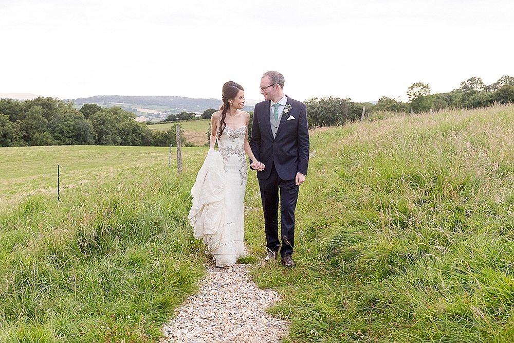 Couple walking through the fields at River Cottage Wedding