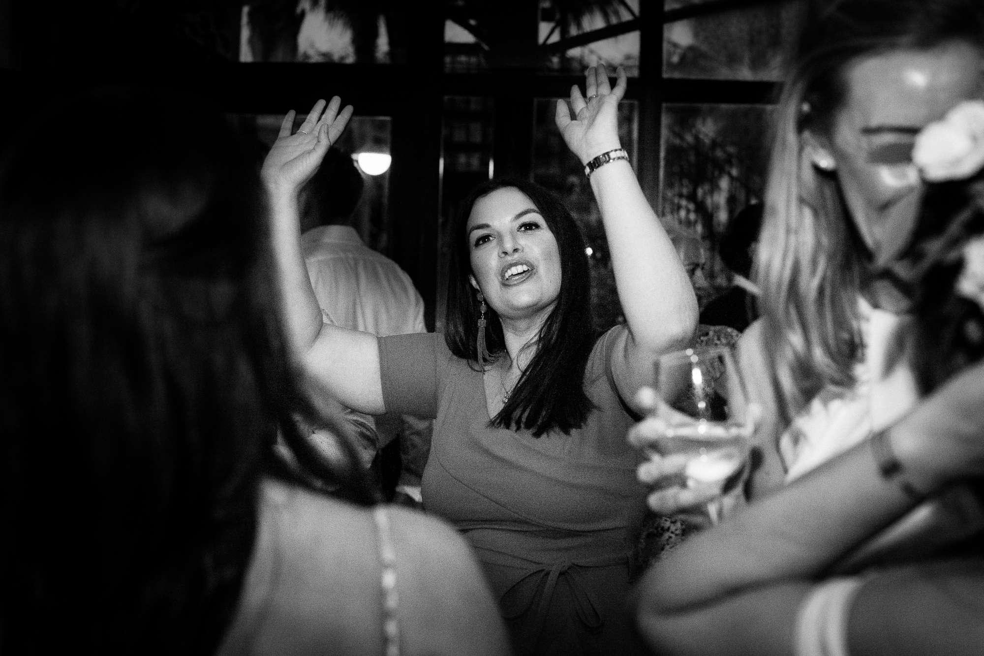 wedding guest dances and raises hands