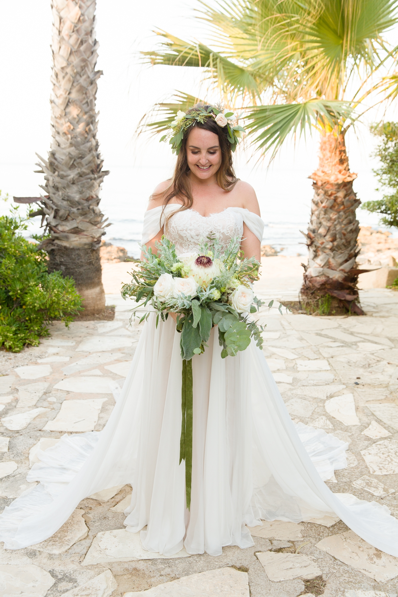 bride stands in front of palm trees in Denia wedding wearing a Moira Hughes dress and flower crown and white bouquet
