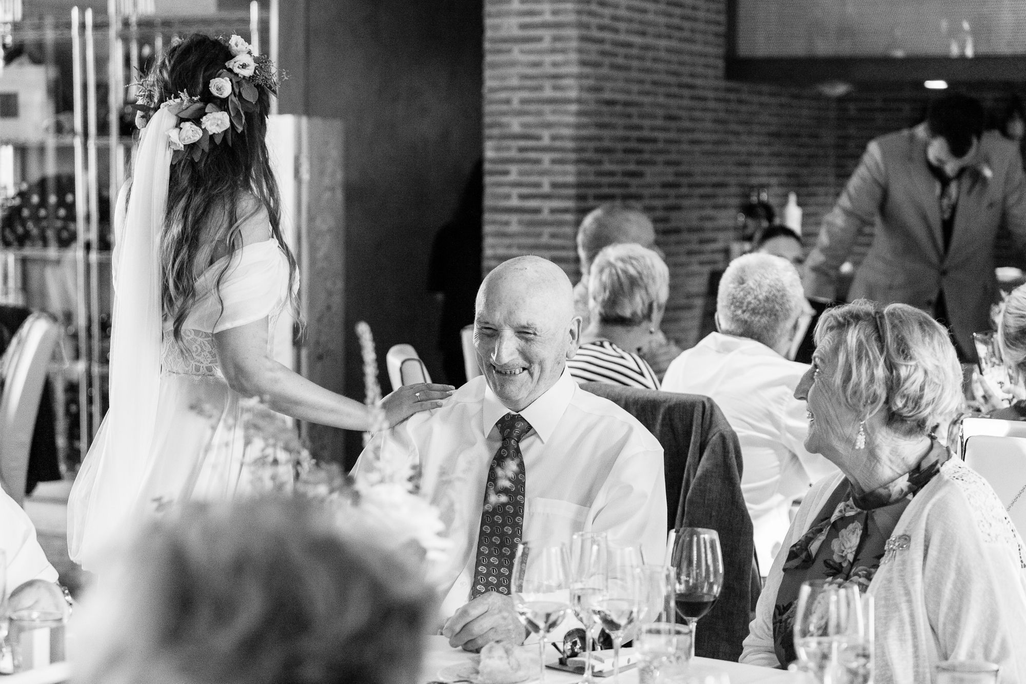 bride touches the shoulder of her grandfather at wedding reception in Denia
