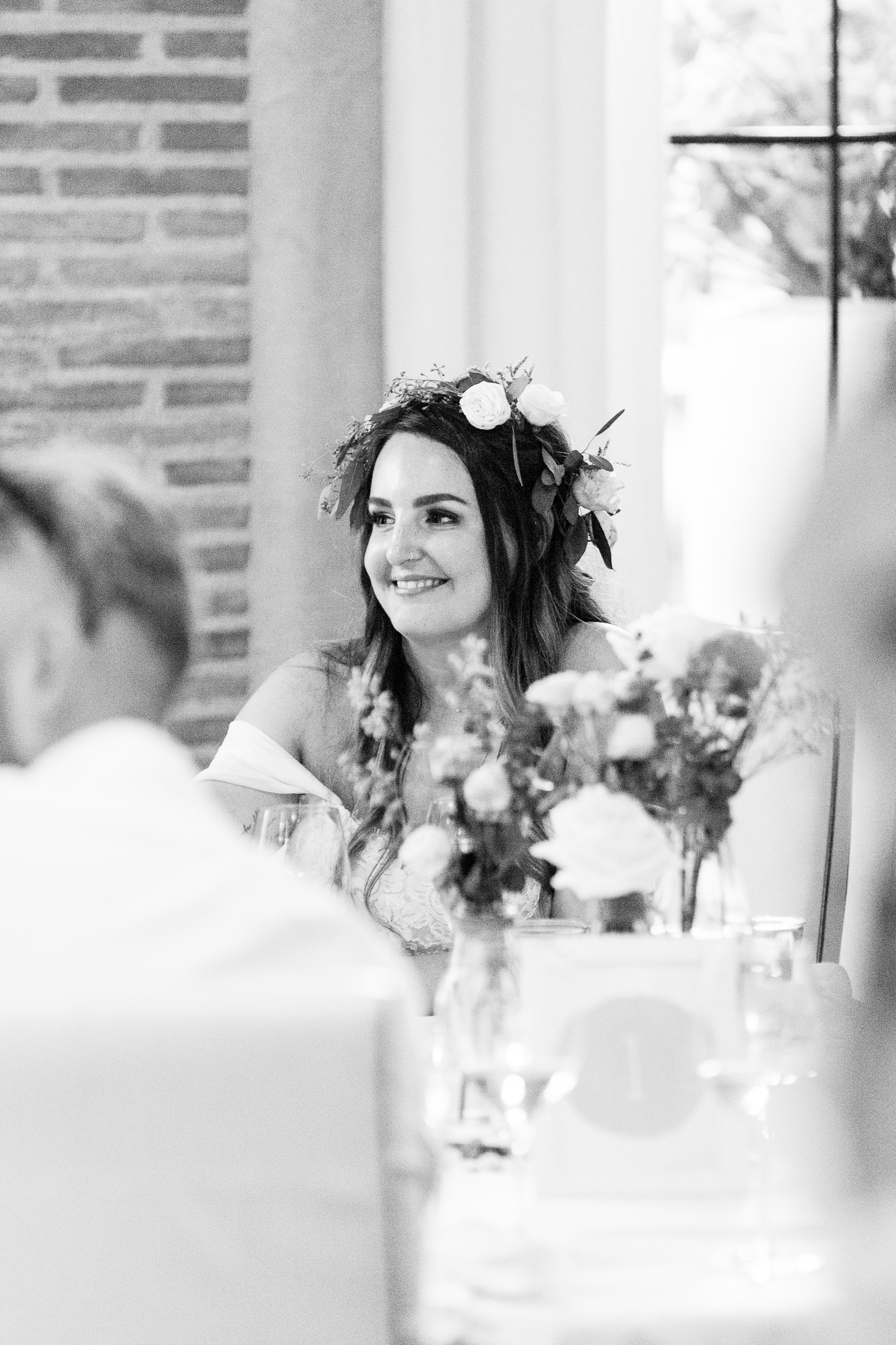 bride in flower crown laughs during wedding speeches at hotel les rotes