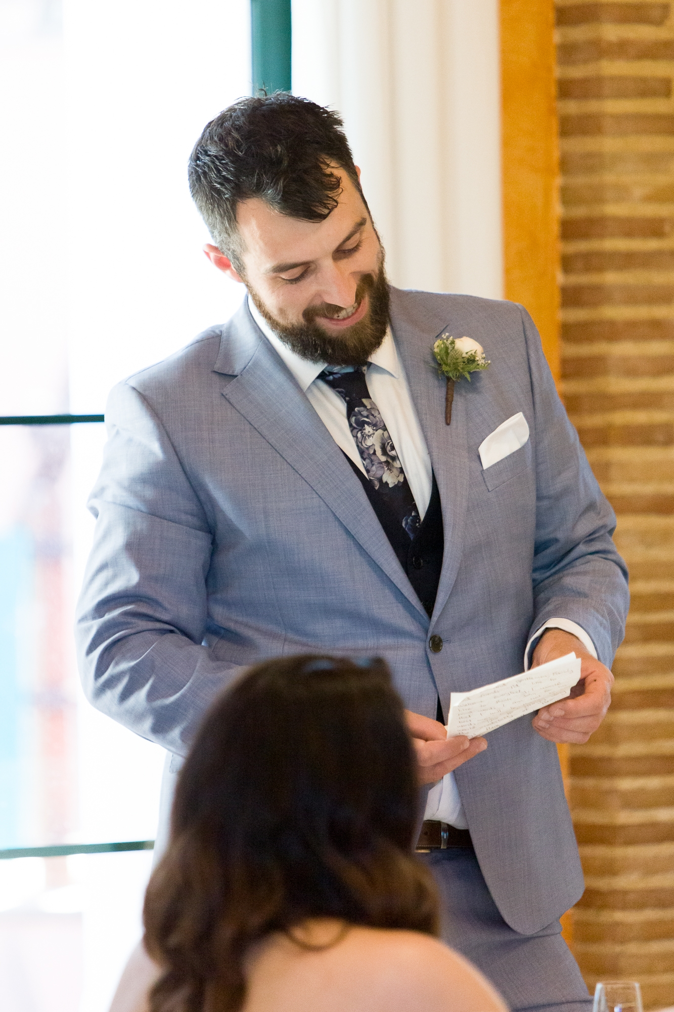 groom wearing light blue suit gives speech at wedding reception in denia