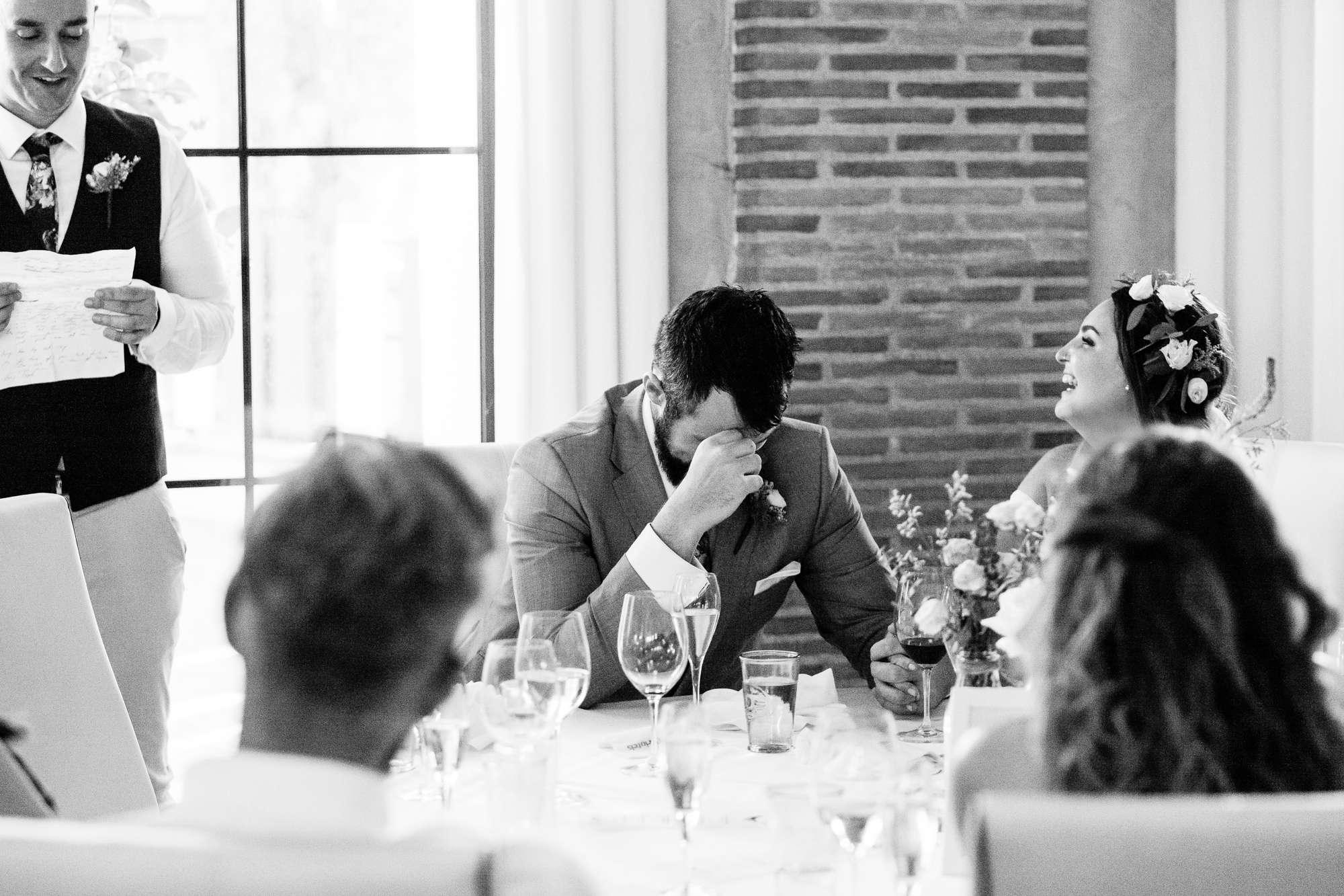 groom hangs his head during the best mans speech at destination wedding in spain