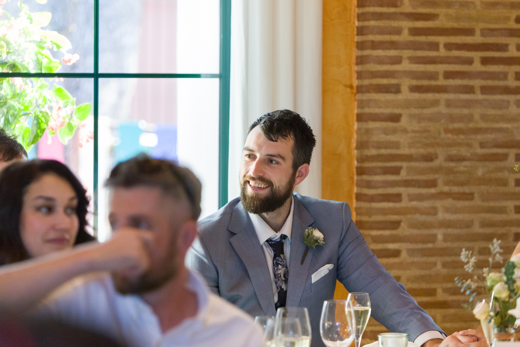 groom laughs in the reception at Hotel Les Rotes wedding