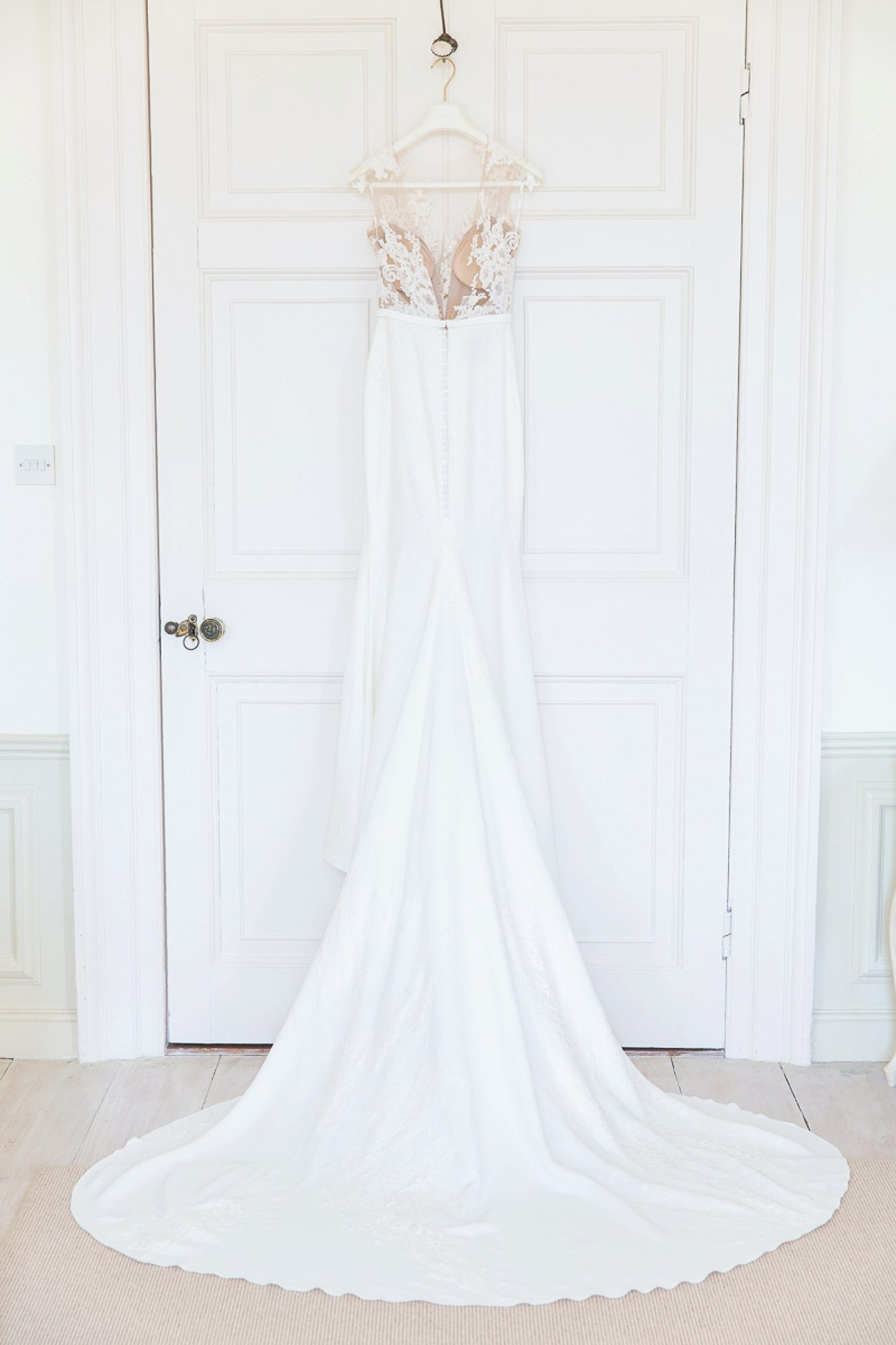 Pronovias wedding dress hanging on door at Pynes House wedding