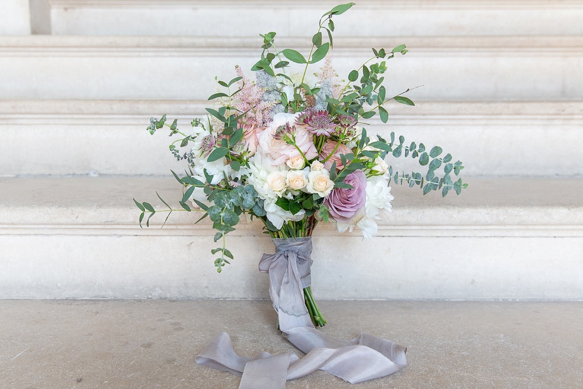 wedding bouquet on the steps of Pynes House in Devon