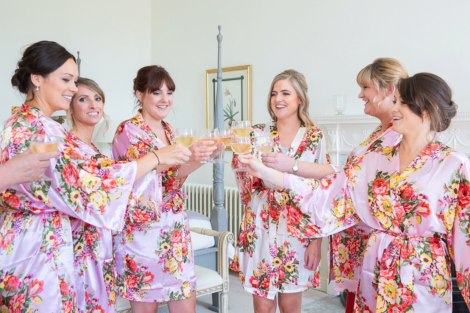 bride and bridesmaids make a toast with champagne in Pynes house in devon