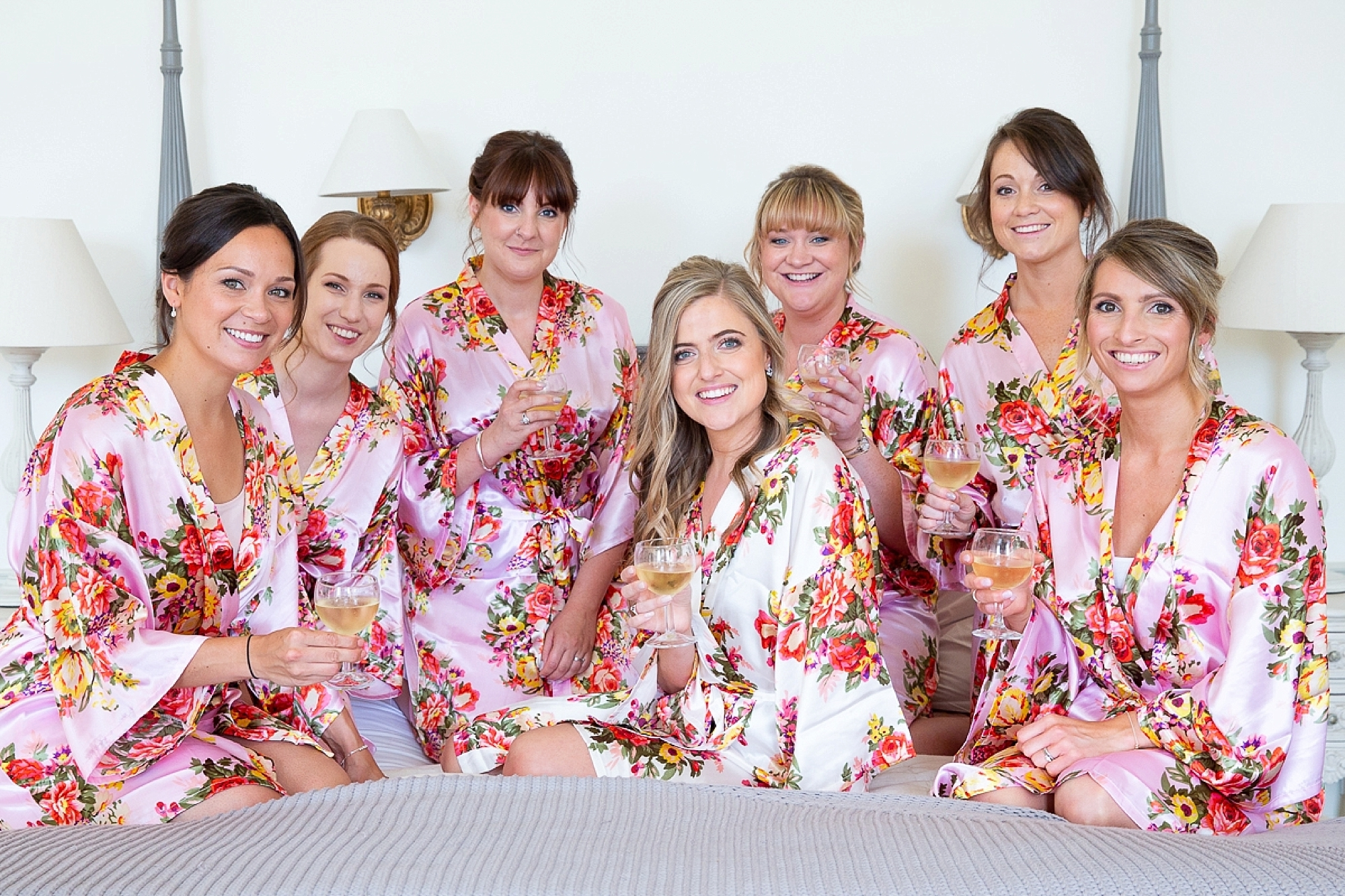 bridal party at wedding in Pynes house sit on bed together