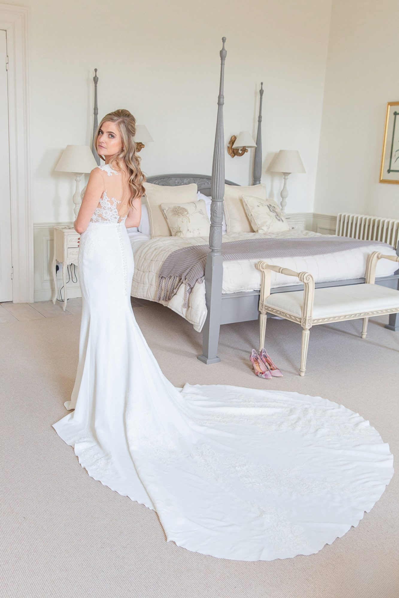 Bride in Pronovias wedding gown looks backwards with a long wedding train