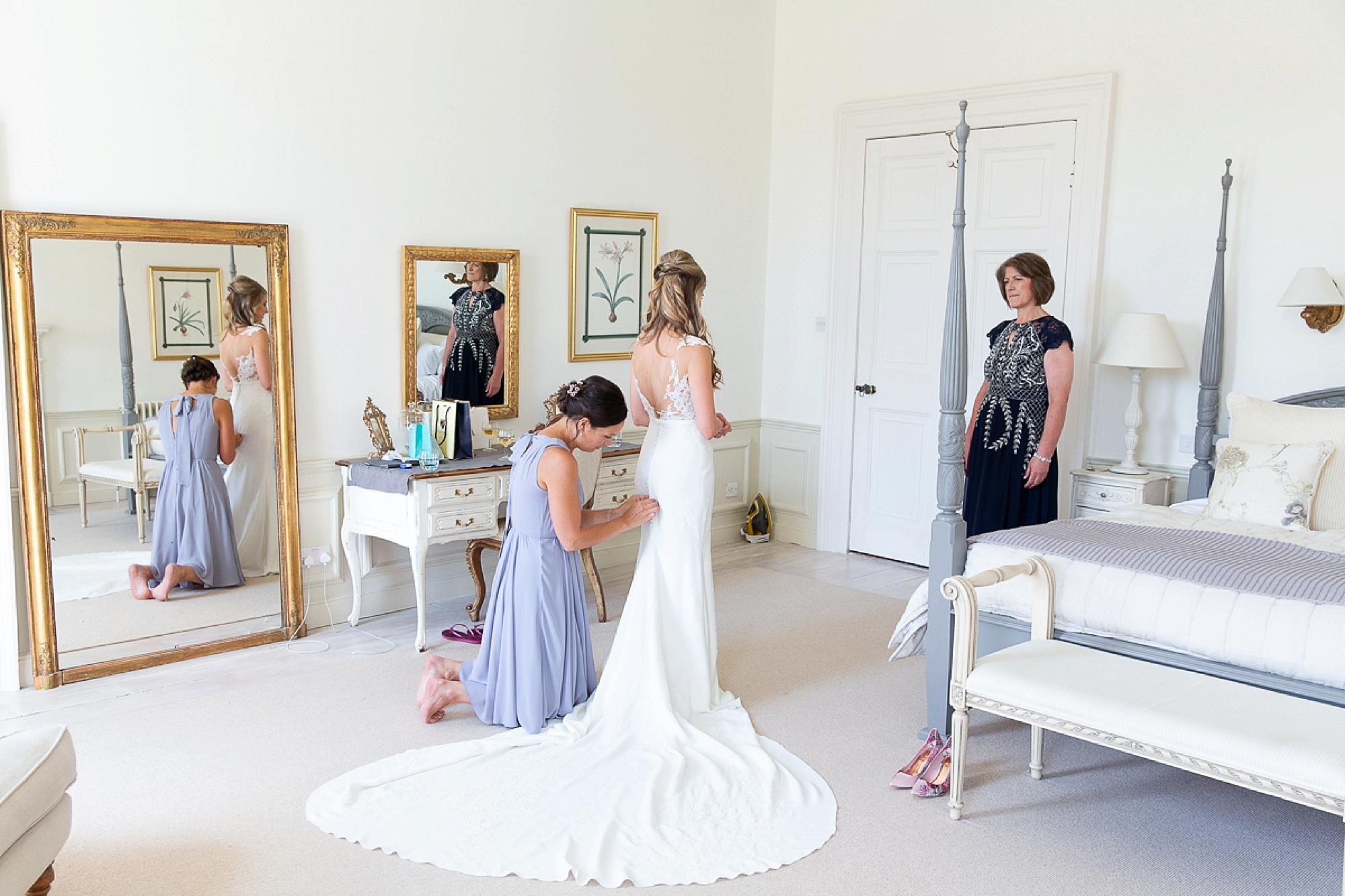 Pronovias bride stands in Pynes House room as her bridesmaid does the back of her wedding dress up