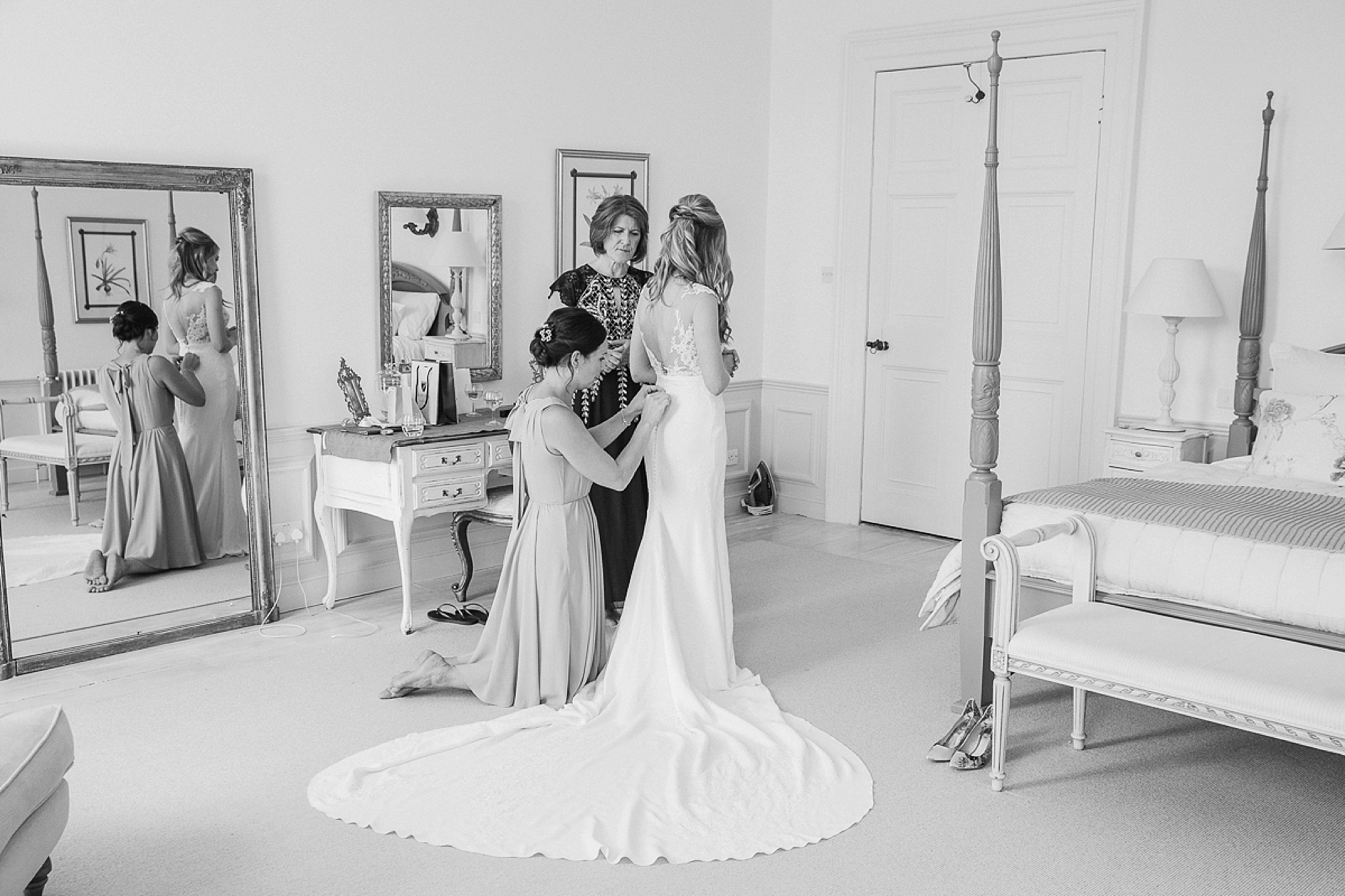 Black and white of bride, mother as bridesmaid kneels on the floor to fasten the wedding dress