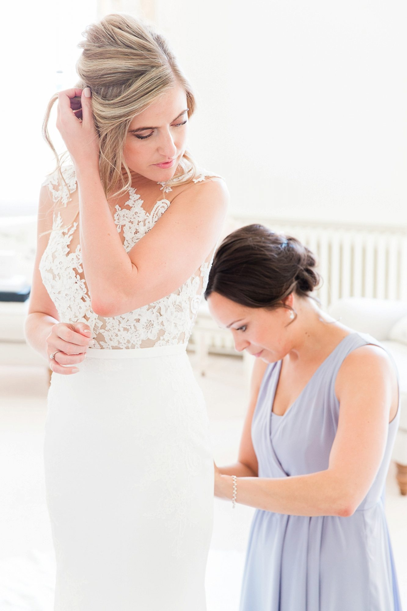 Bride holds hair as bridesmaids kneels on the floor behind and fastens her Pronovias dress