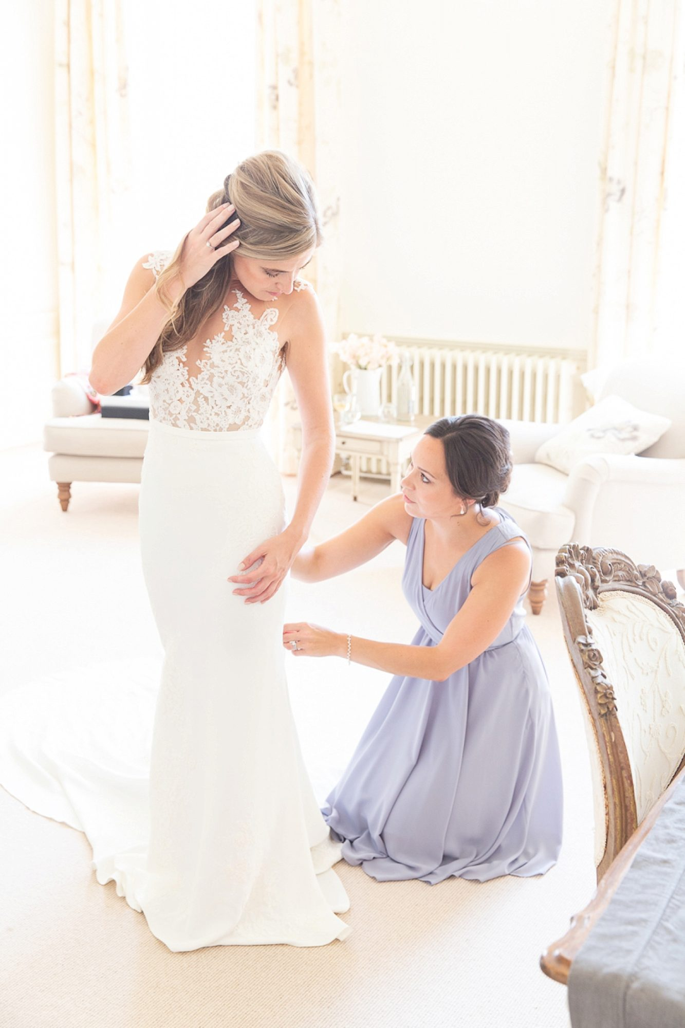 Bride turns holding hair to kneeling bridesmaids who fixes her Pronovias dress