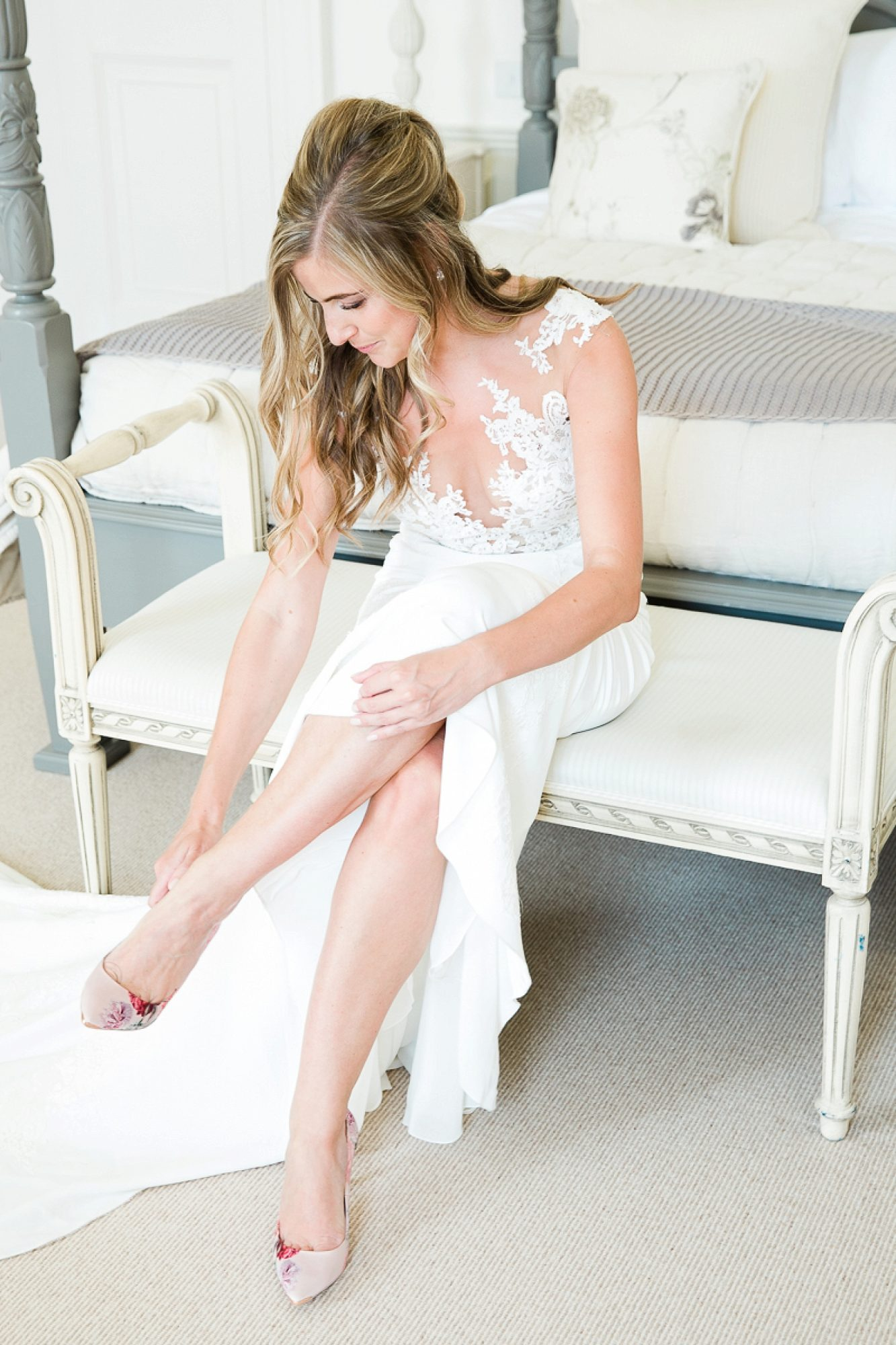 Bride sits in a pronovias wedding gown and puts on her jimmy Choo shoes