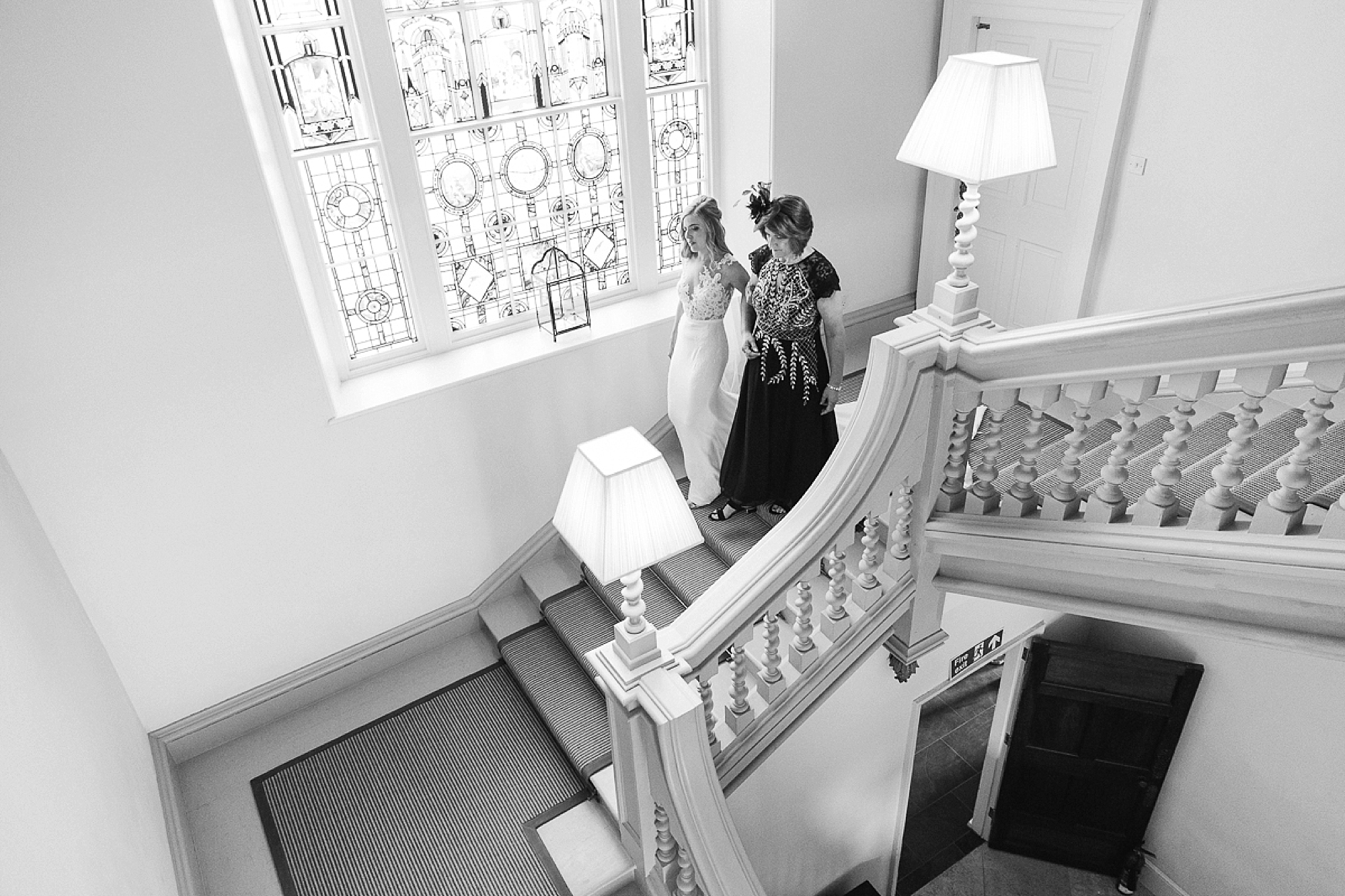 mother and bride walk down the stairs at Pynes House before the wedding