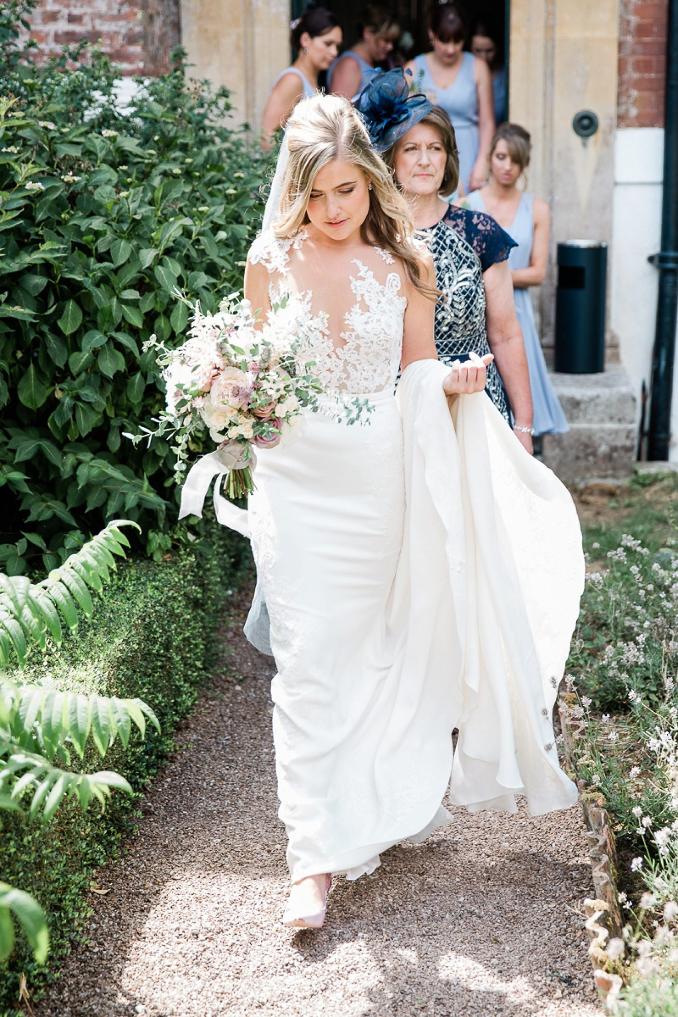 Bride holds dress over arm as she walks the gardens at Pynes house before her wedding ceremony