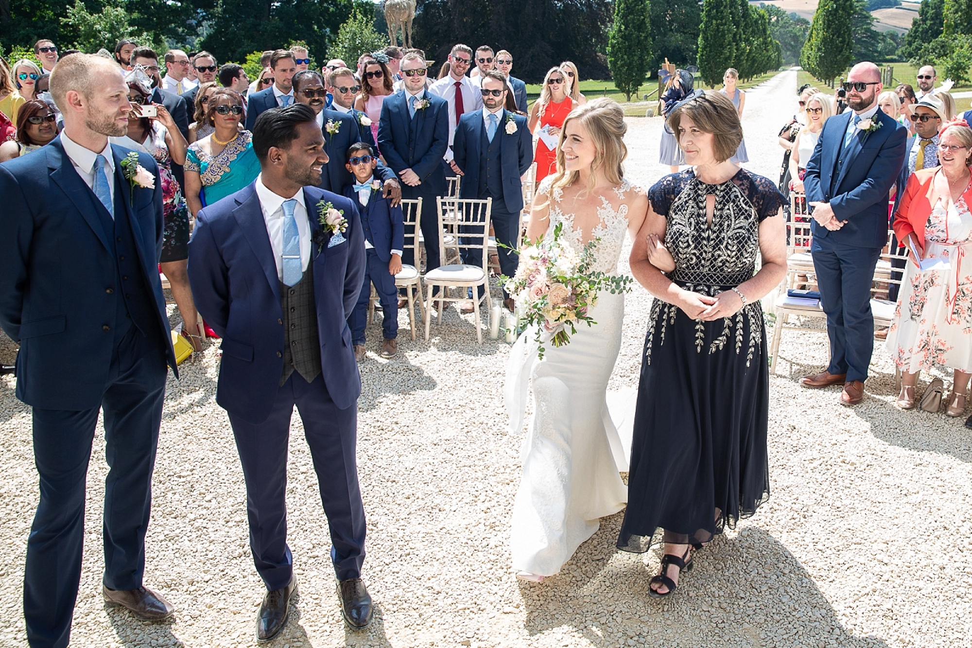 bride and mother walk up to groom in outdoors wedding ceremony at Pynes house in devon